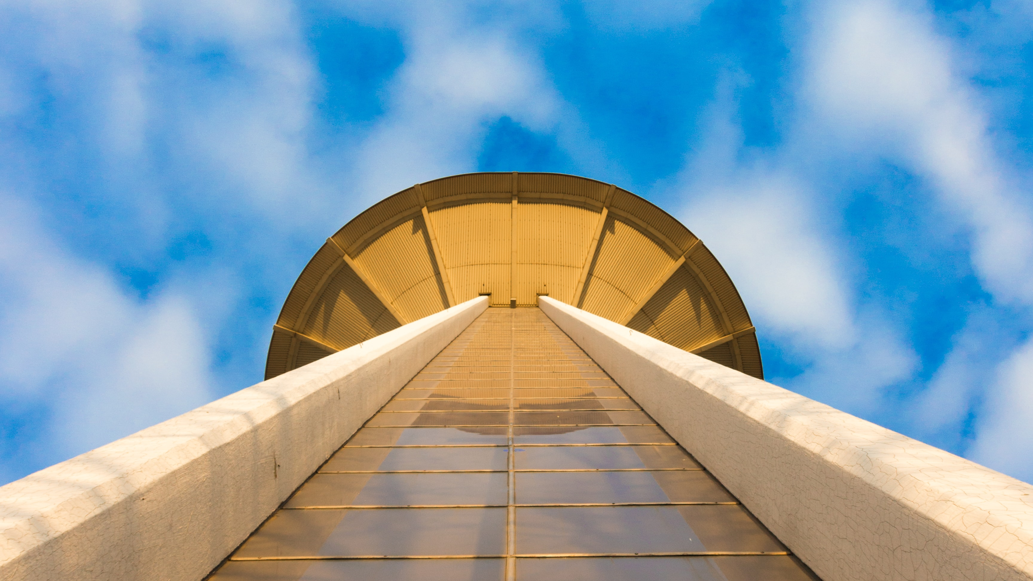 worm's eye view photography of tower under cloudy sky during daytime