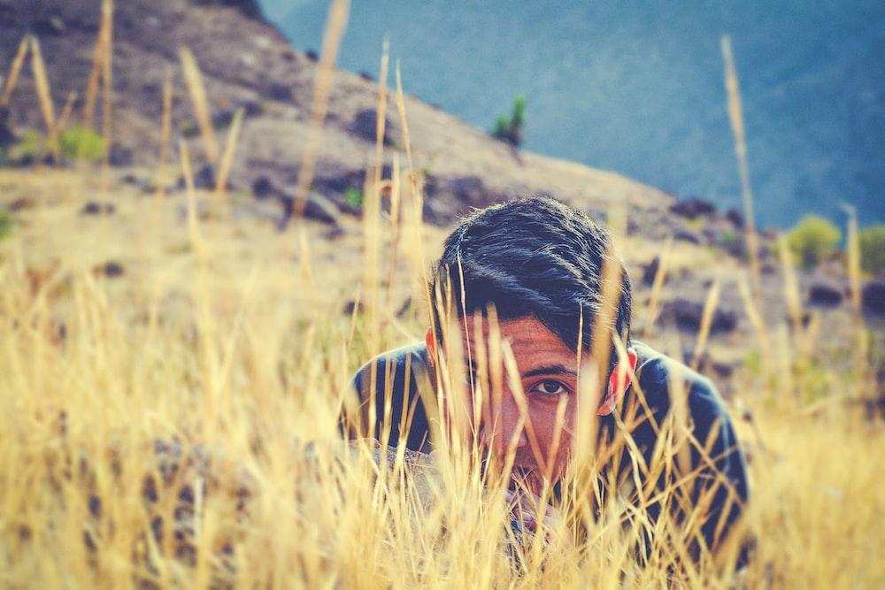 man wearing black shirt hiding on green grass field at daytime