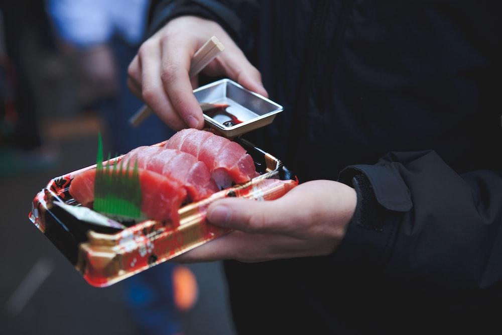 person holding tuna sashimi