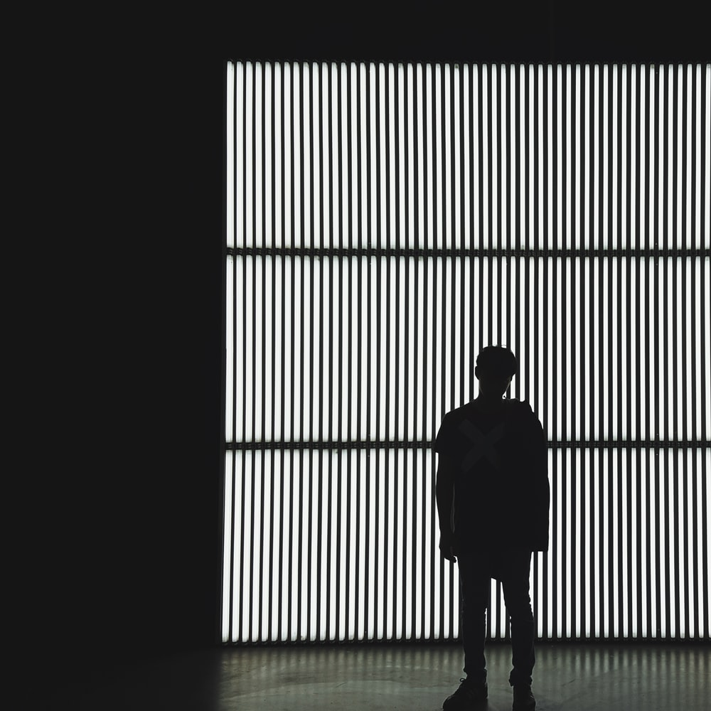 silhouette photo of a person standing near wall in dark room