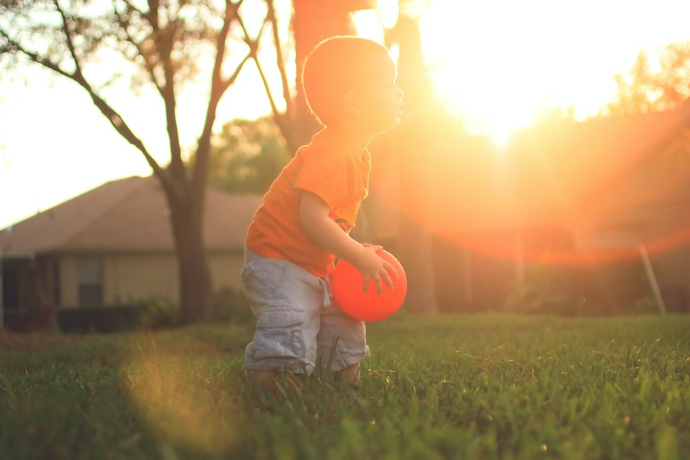 boy holding orange balloon