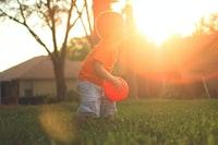 boy holding orange balloon