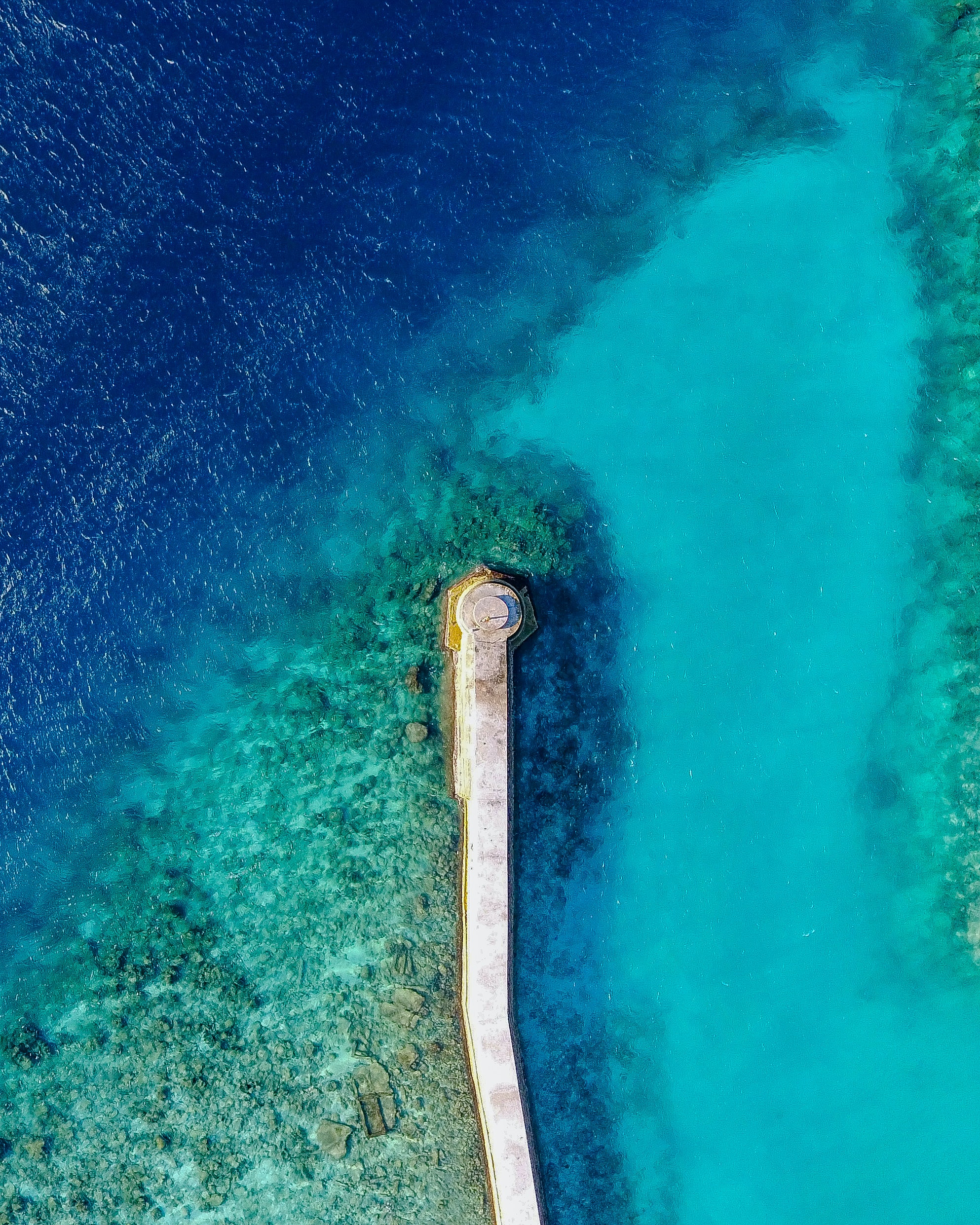 A drone shot of a long jetty on a blue coral reef