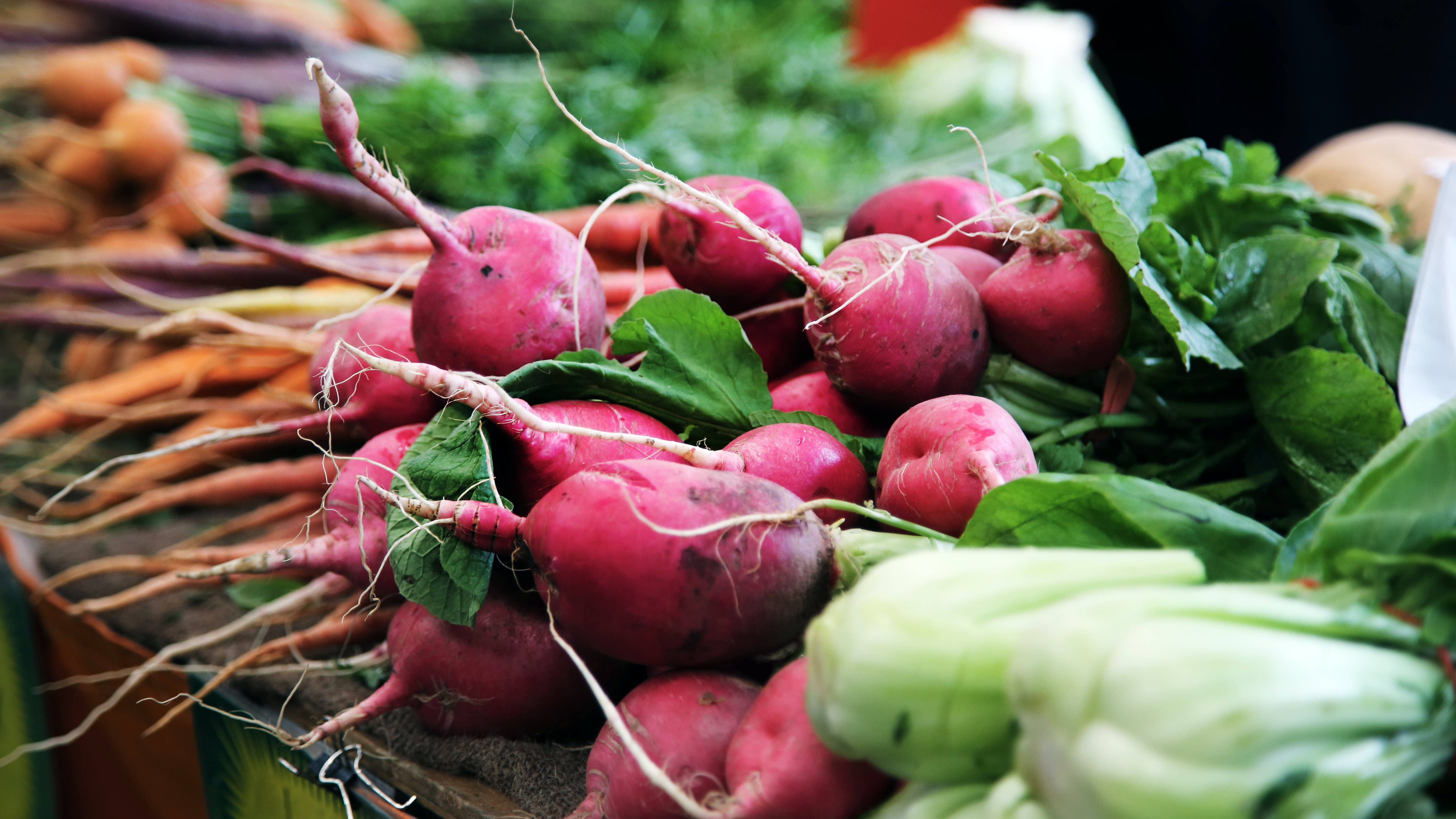 Radishes and other vegetables in an open air market in the city