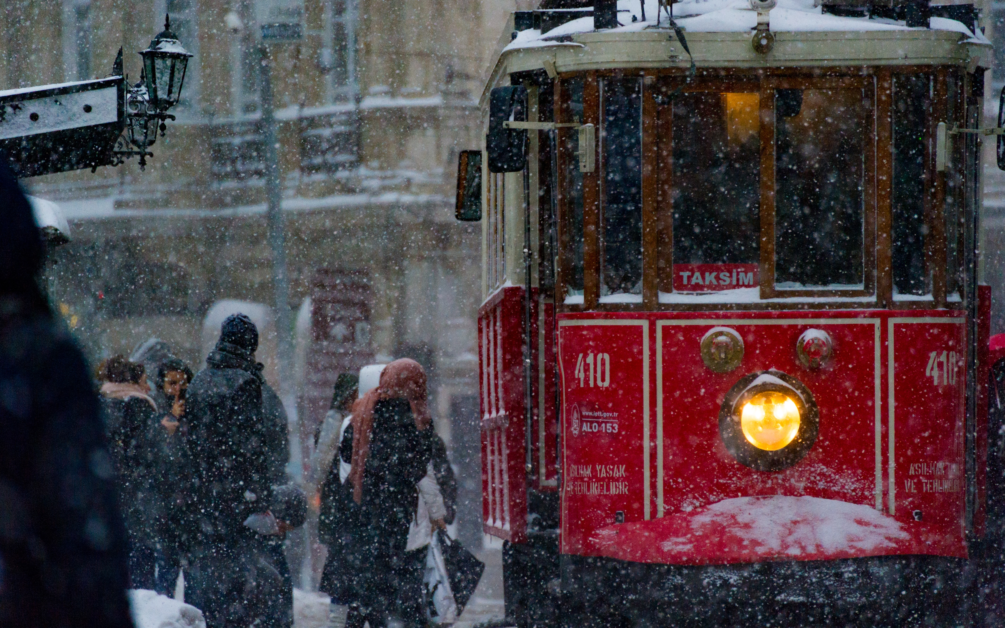 A red trolley picks up passengers in winter clothing during snowfall