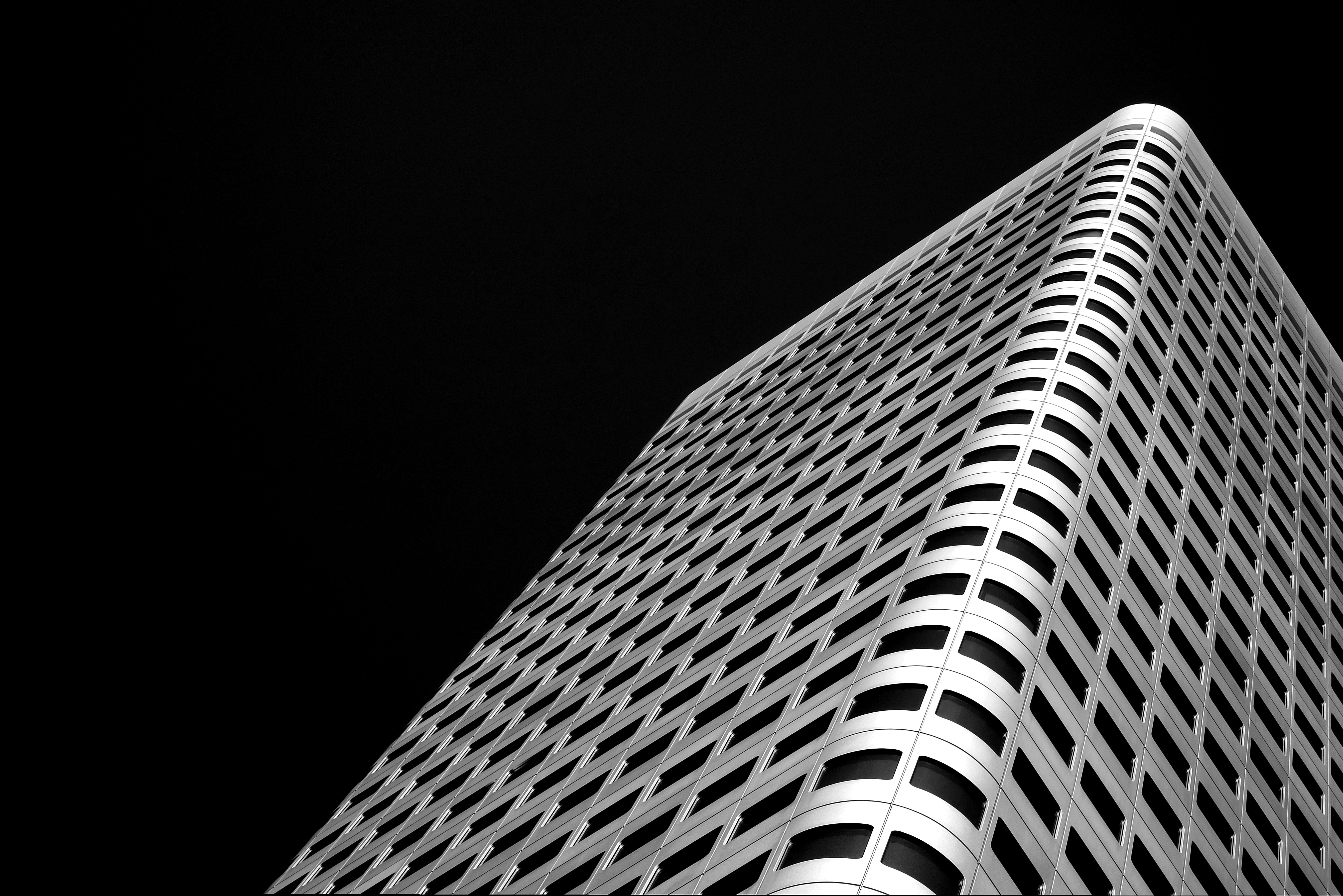 A desaturated shot of a modern office building with rounded corners in Frankfurt