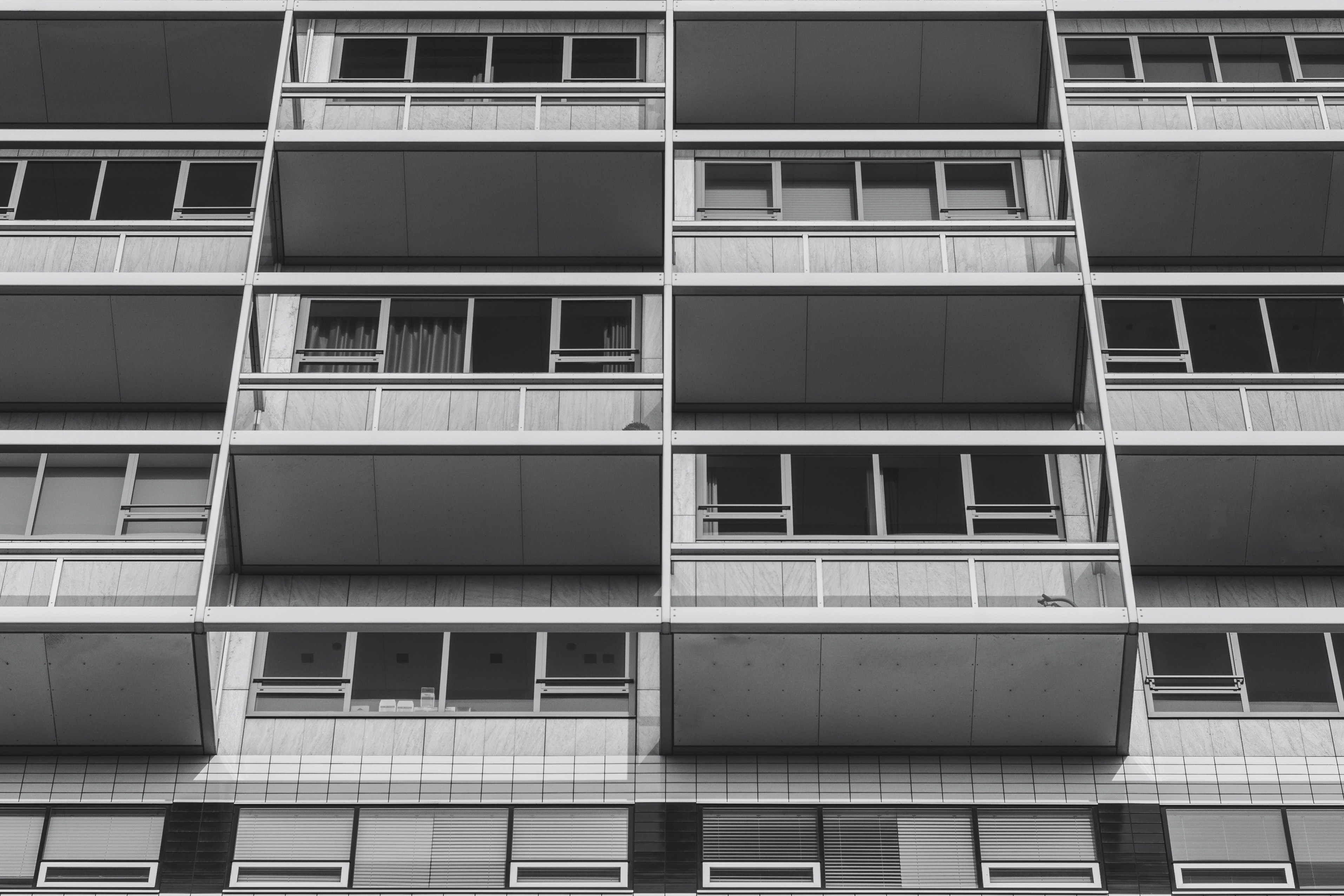 Black and white shot of urban building with balconies and windows