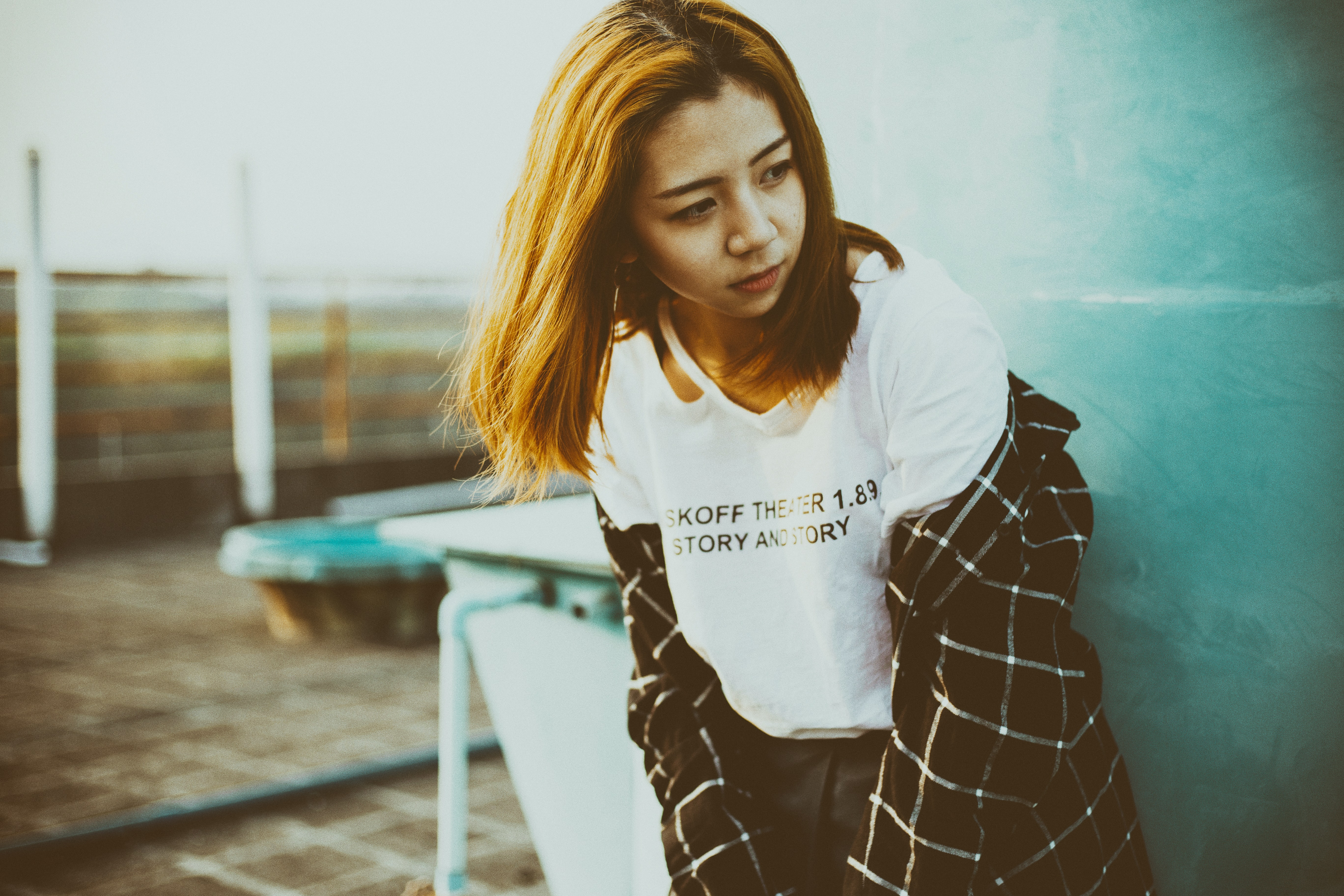 Woman in a graphic tee shirt and flannel looking away