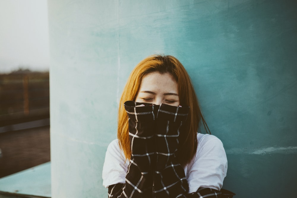 woman leaning on wall covering her mmouth