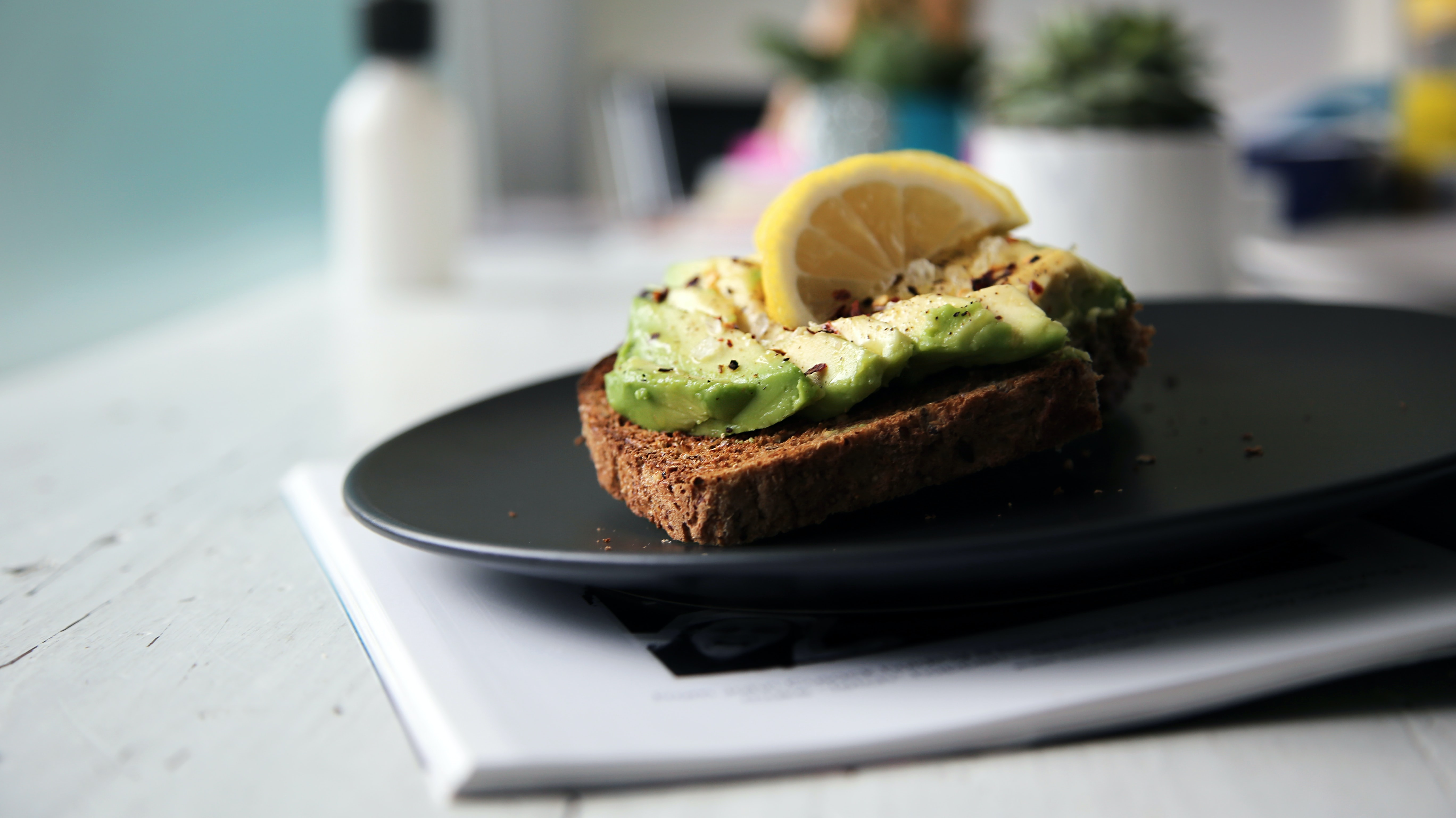 Slice of avocado toast with herbs and lemon