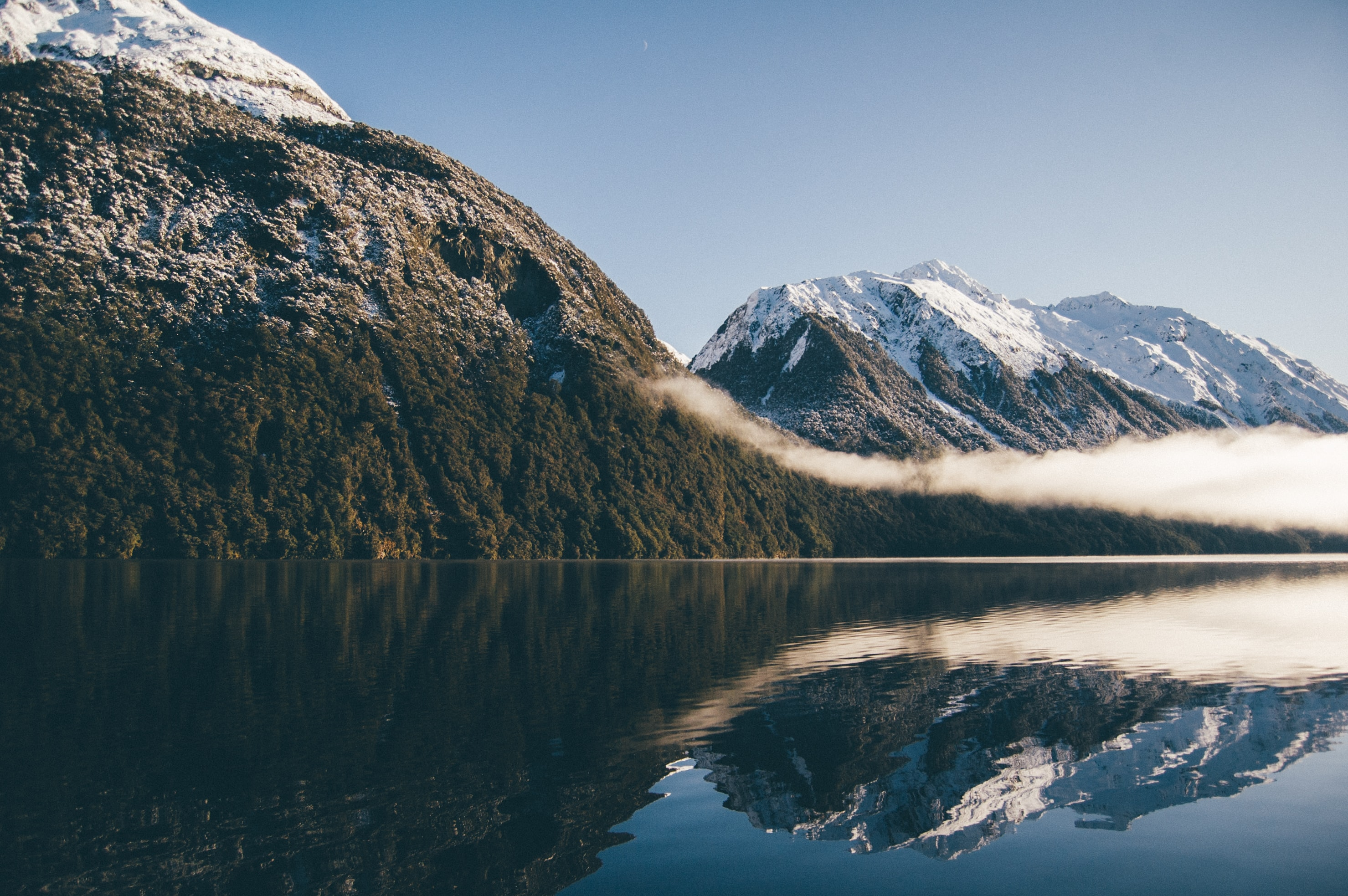 Majestic mountains reflect into a serene lake in winter