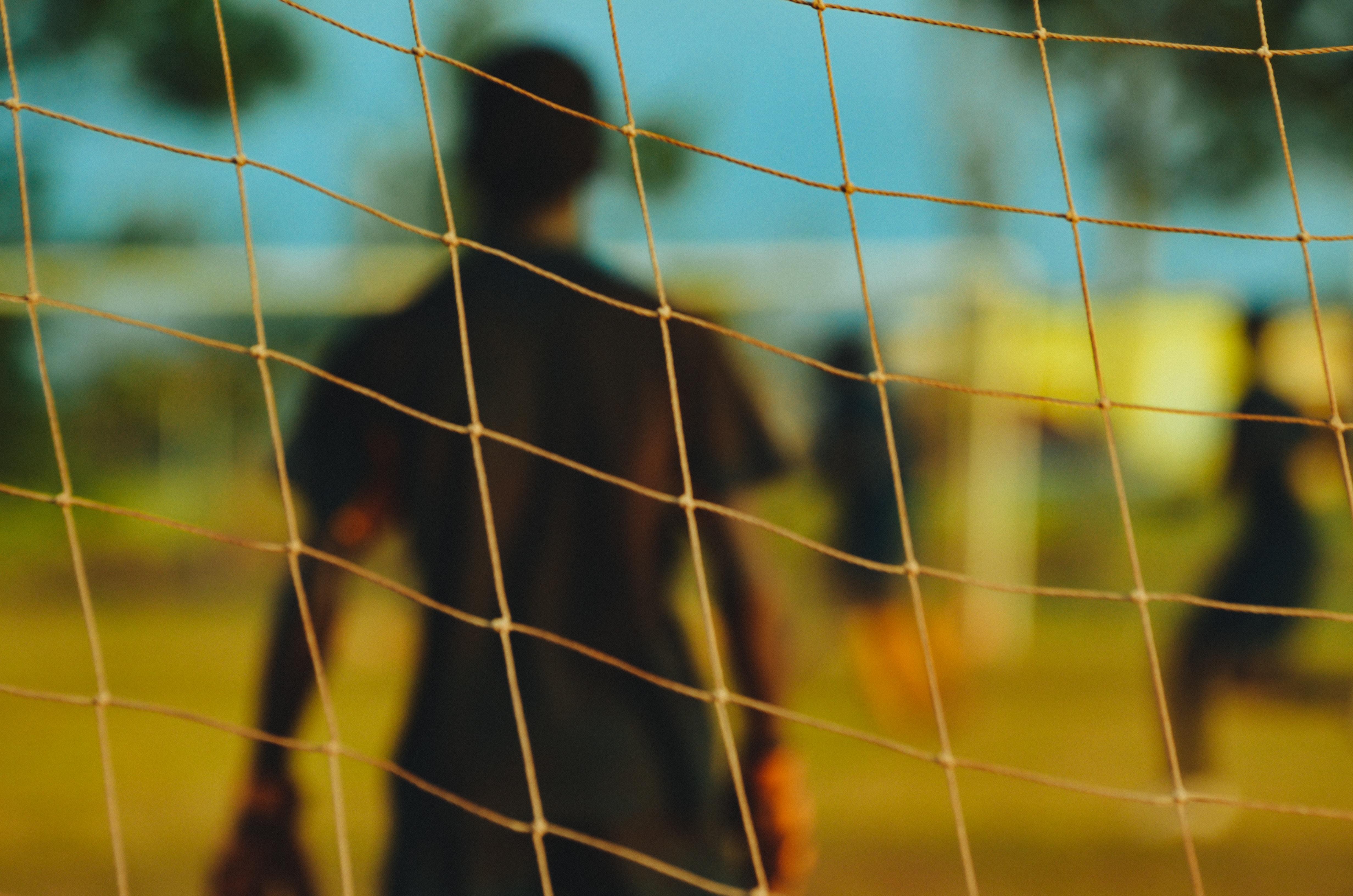 Blurred goalkeeper through the focused goal net in New York, Texas.
