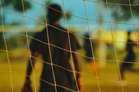 man in black T-shirt through soccer goal post