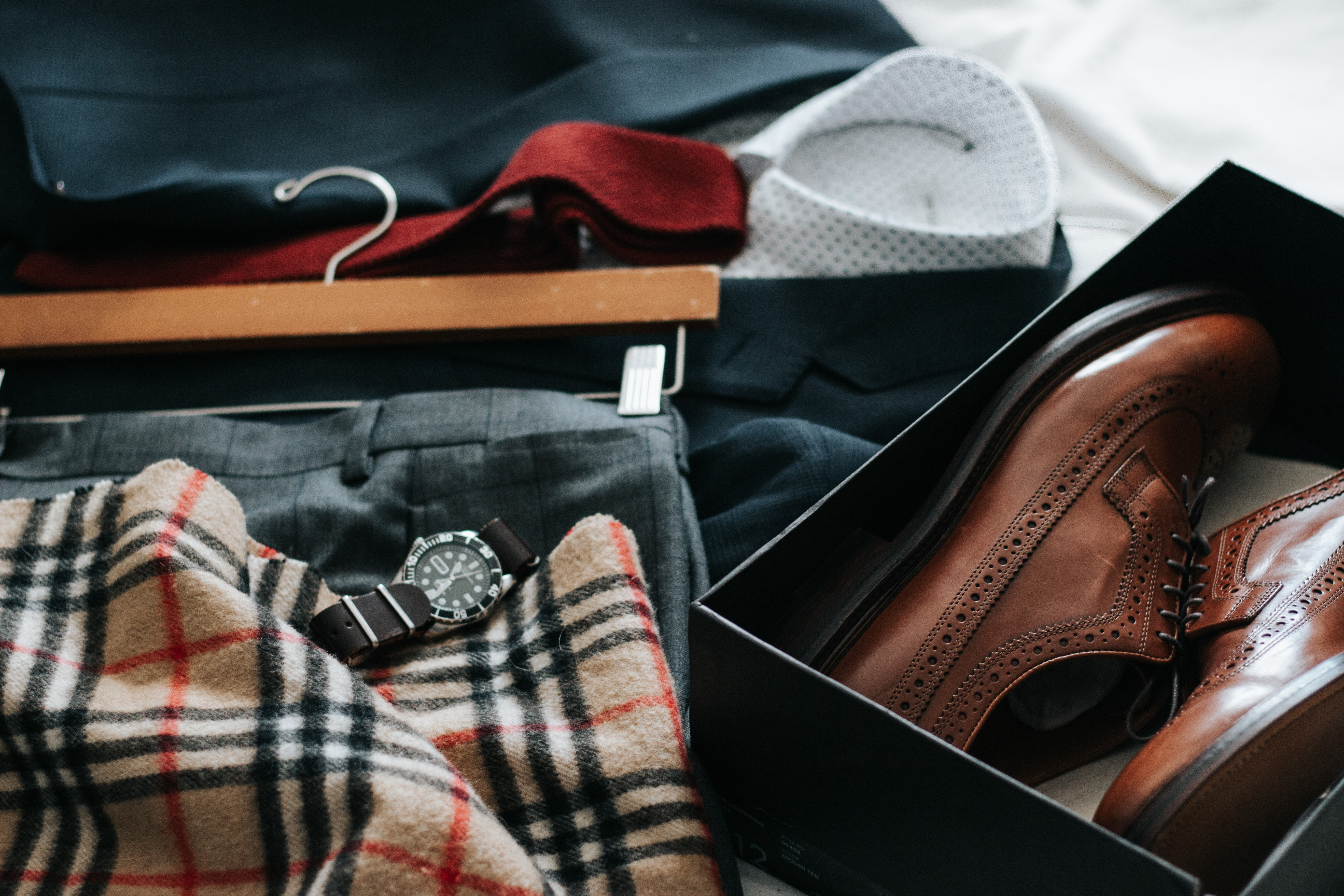 A pair of leather shoes in a box next to a suit jacket and a watch