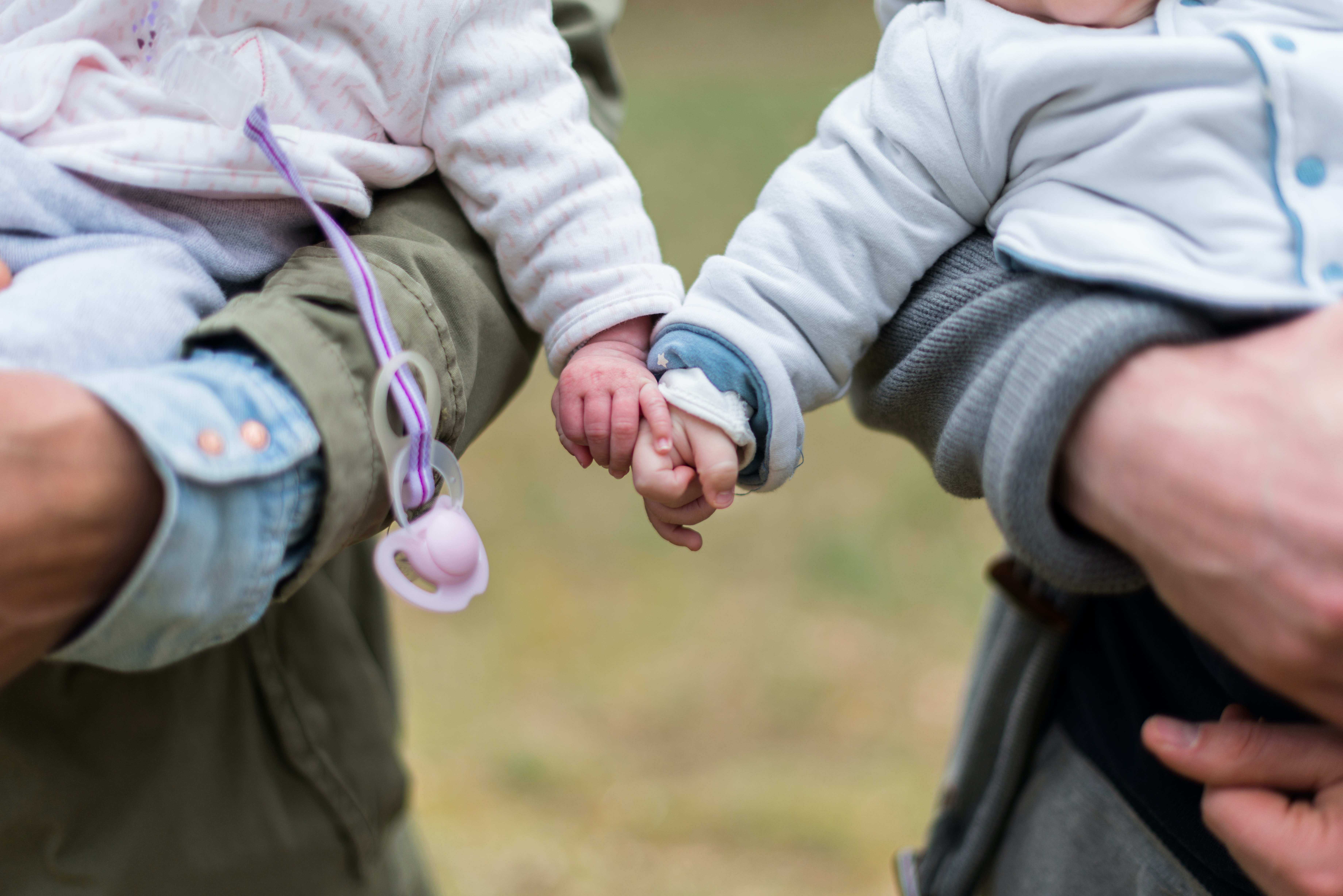 Parents each holding a young child, and the children reach out to touch each other's hands