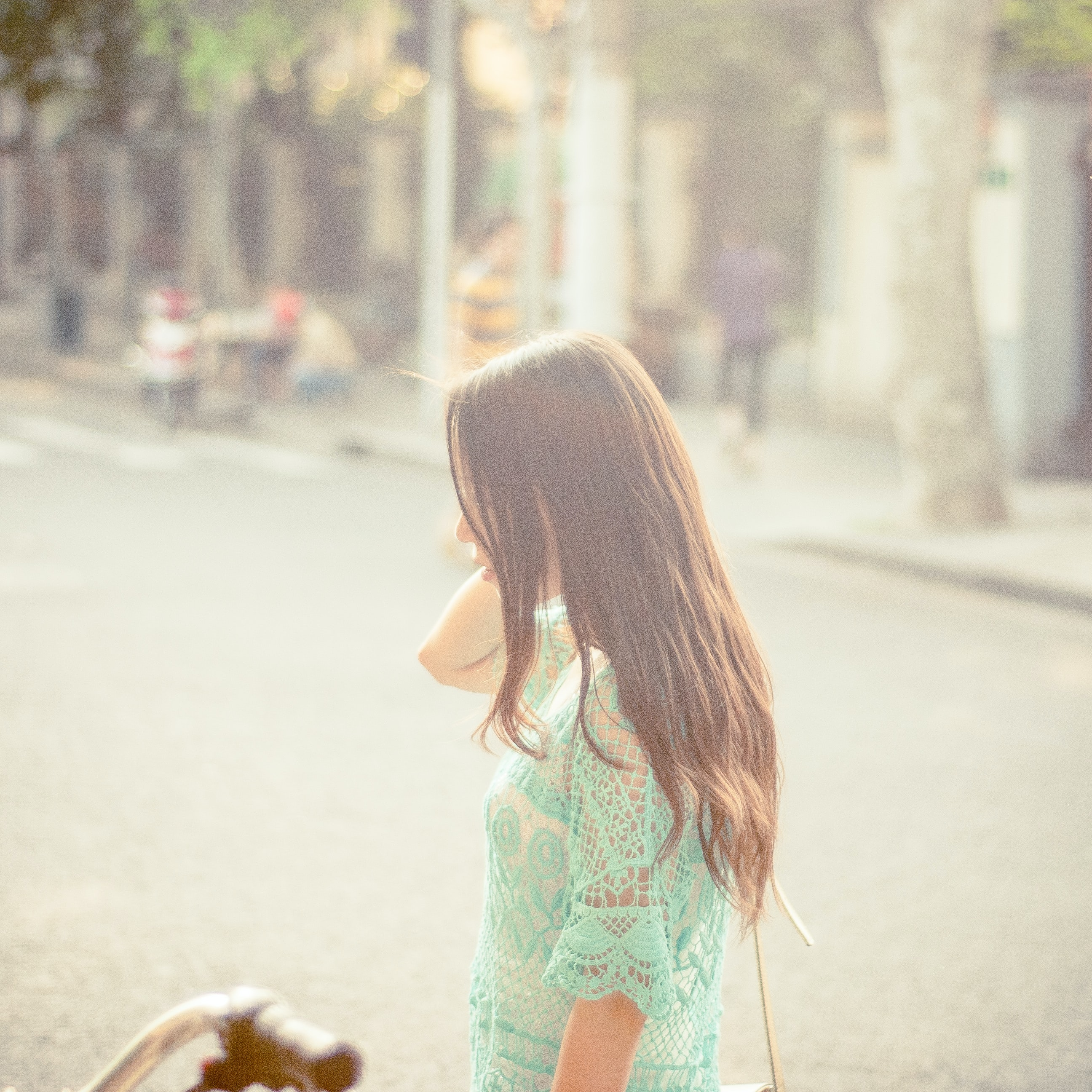 A woman in profile in a turquoise lacy top by a city street in bright sunlight