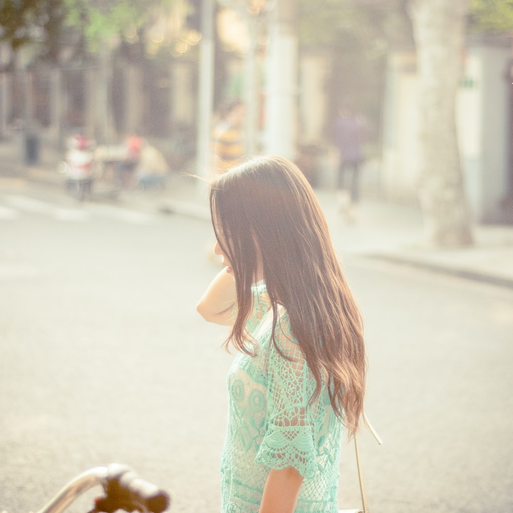selective focus photo o woman wearing green short-sleeved top standing on roadway