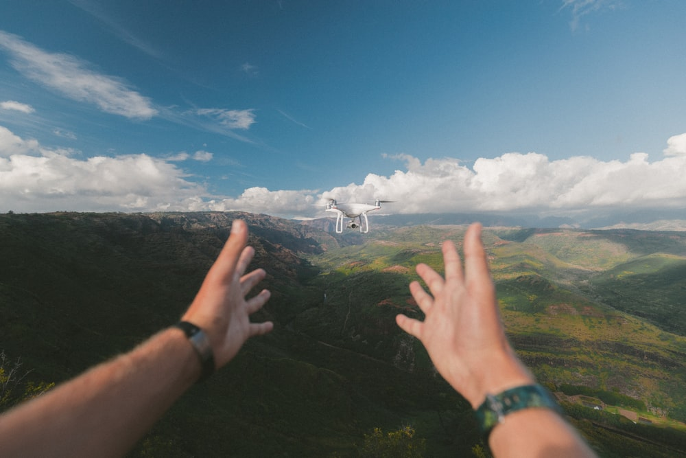 person pointing both hands on white drone during daytime