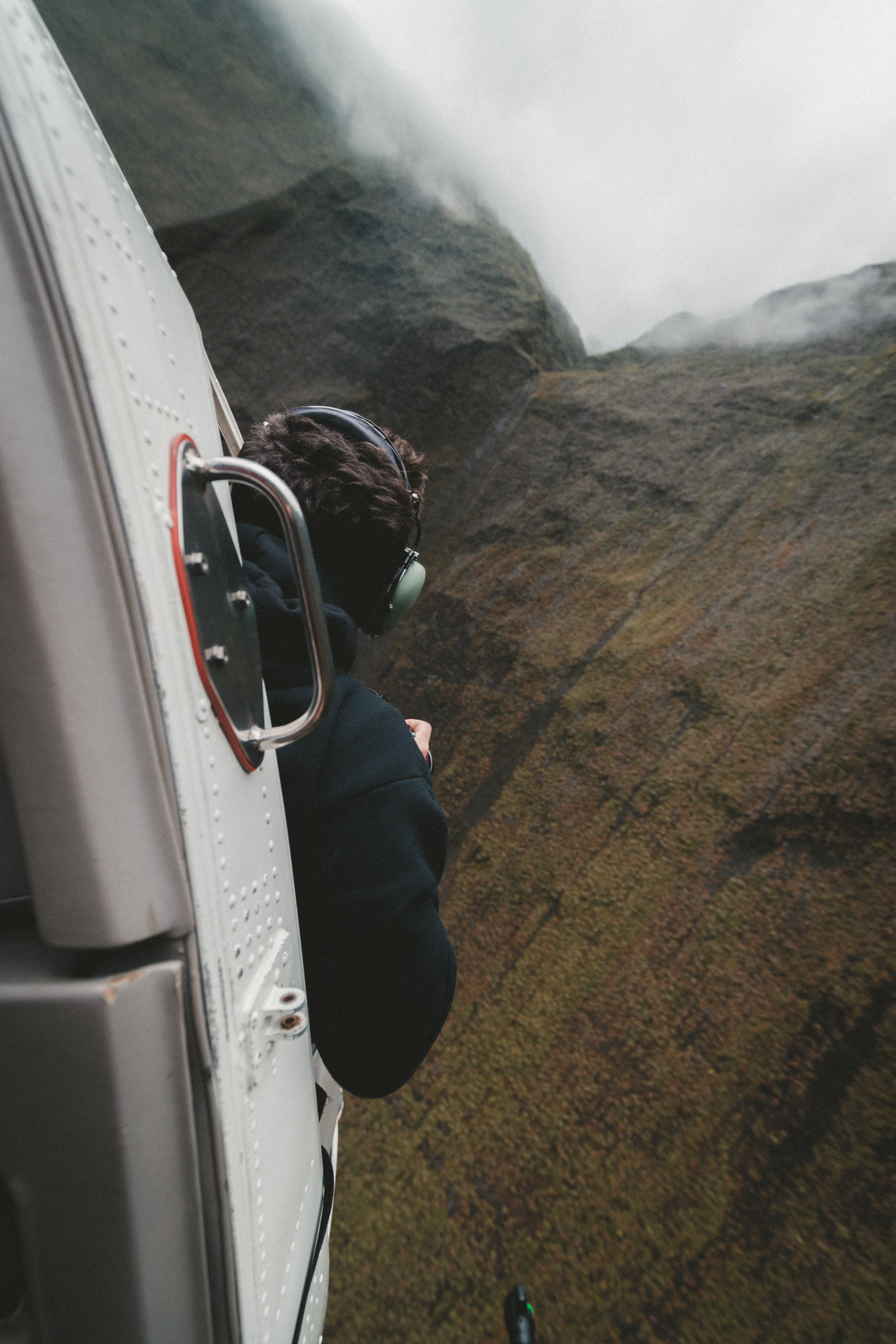 A man in earphones looking out of a helicopter flying next to a mountain