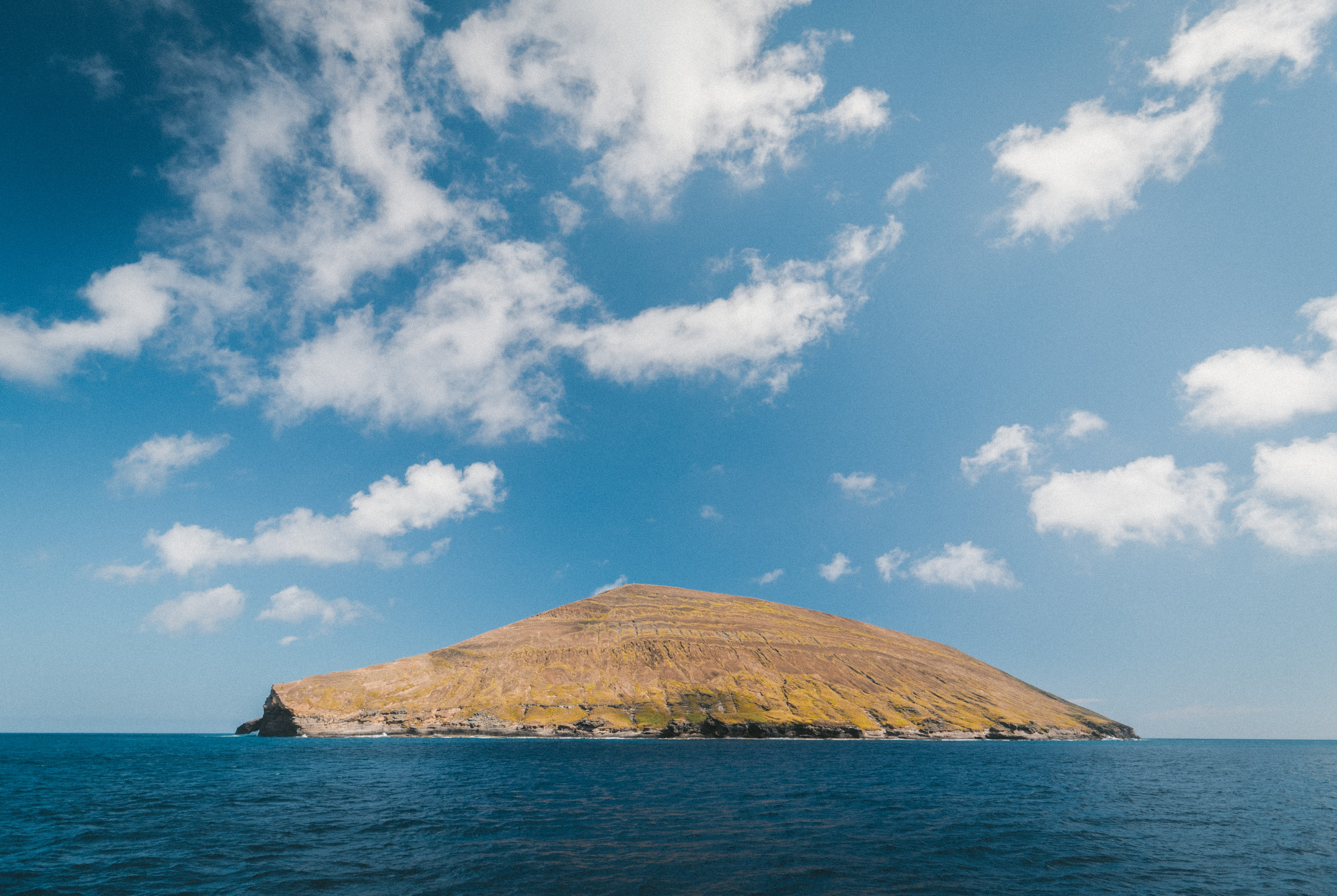 A small brown, grassy island in the middle of the blue ocean with a bright blue sky