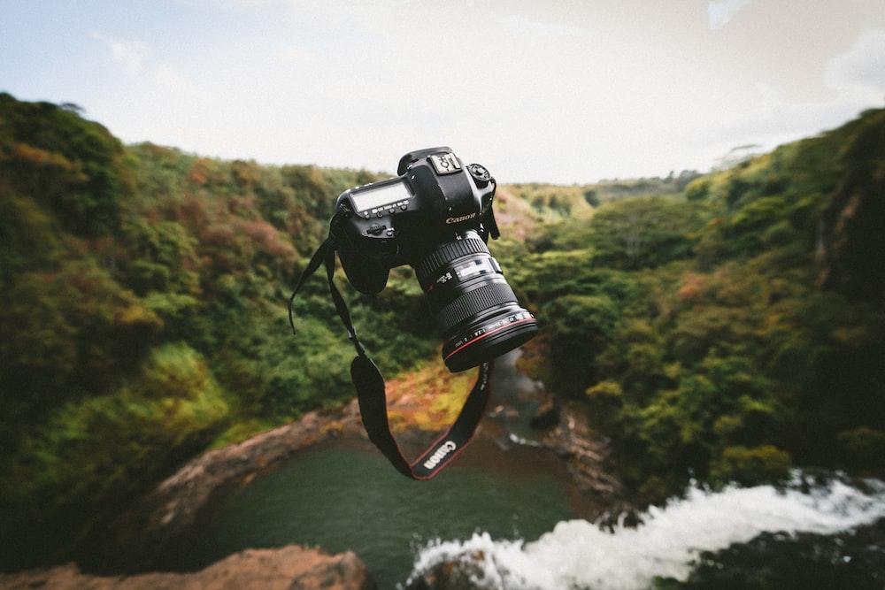 trowed black Canon DSLR camera