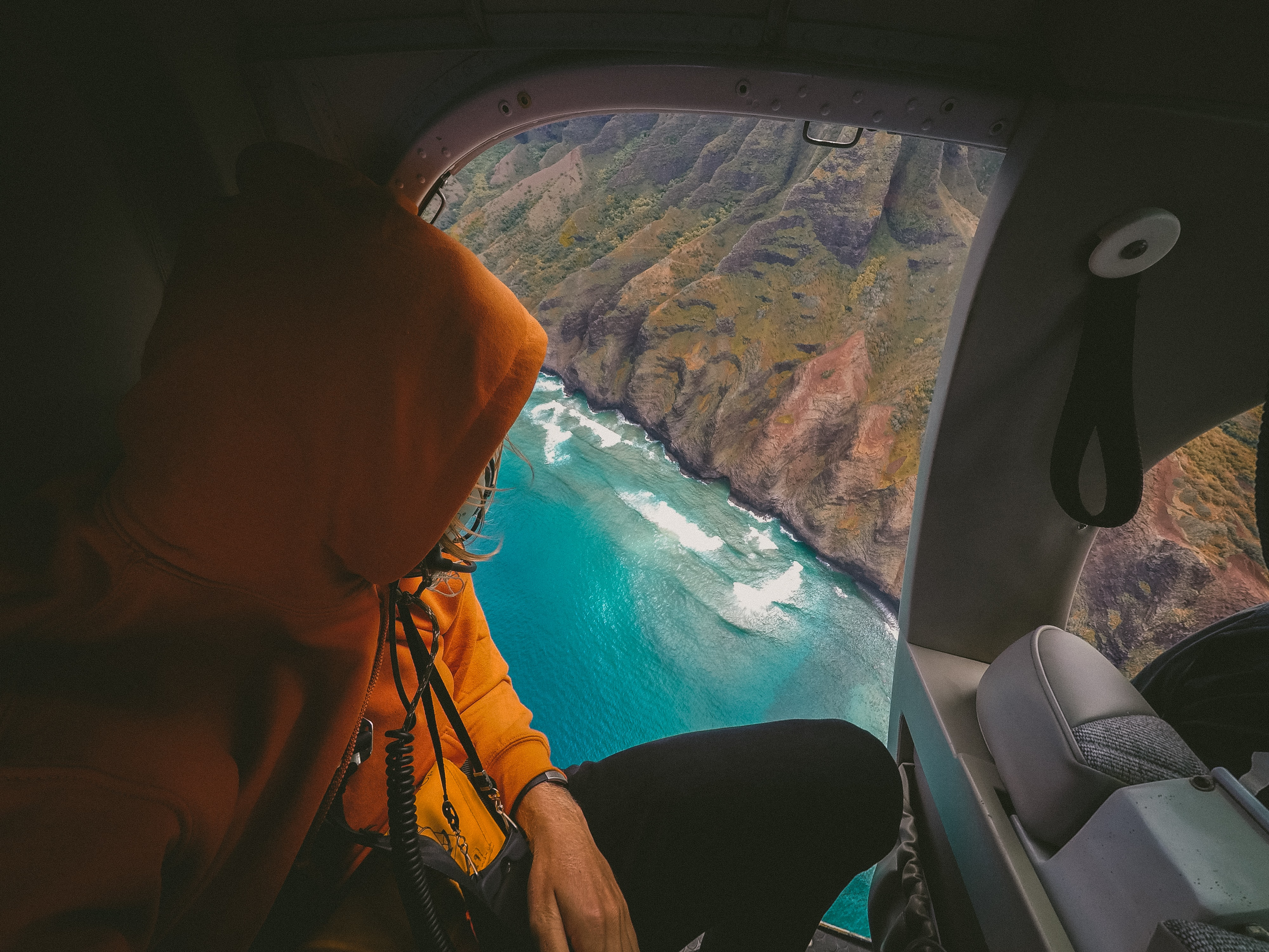A person in an orange parka sitting in a helicopter with an azure coast visible in the window