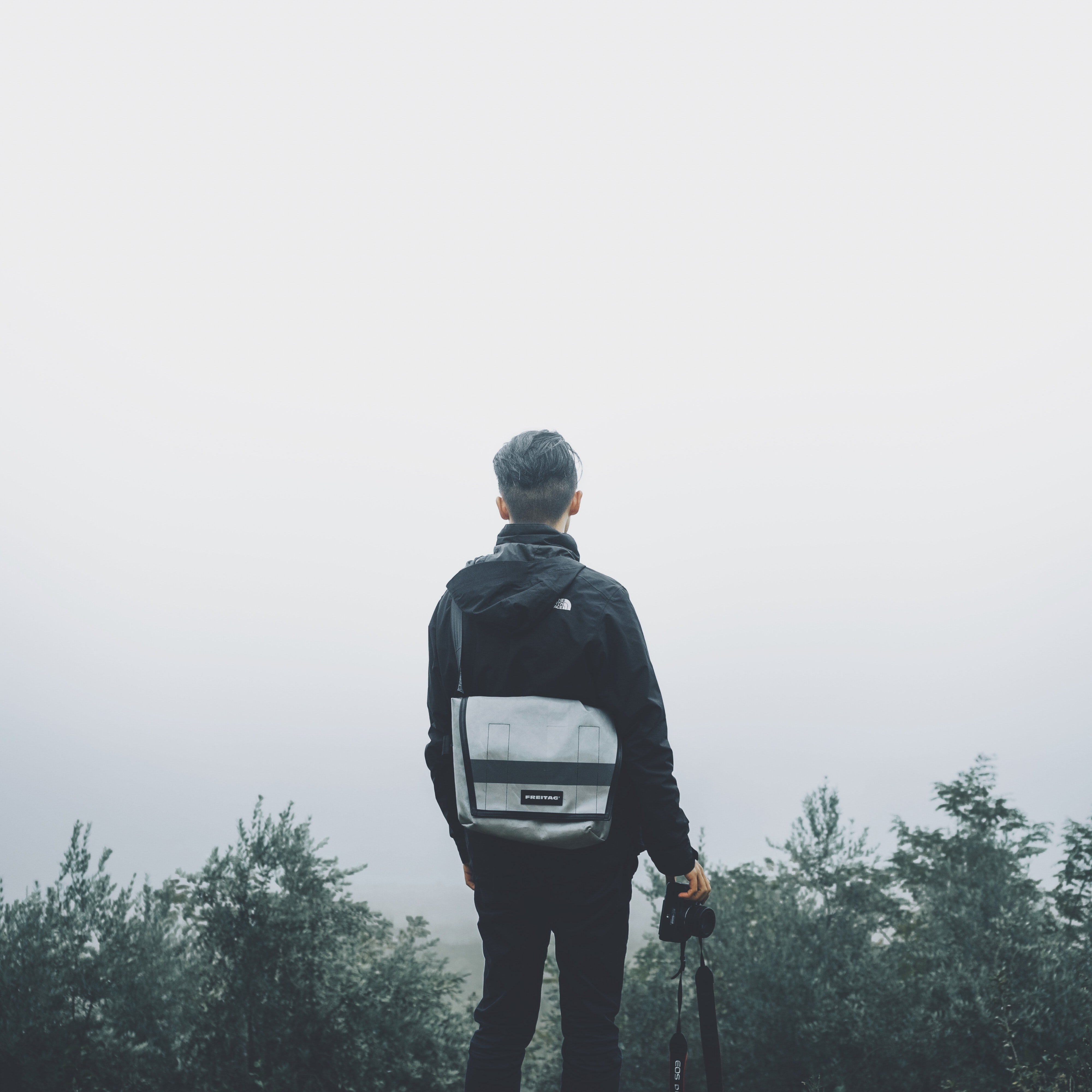 A man standing out into the foggy clouds from the top of a mountain