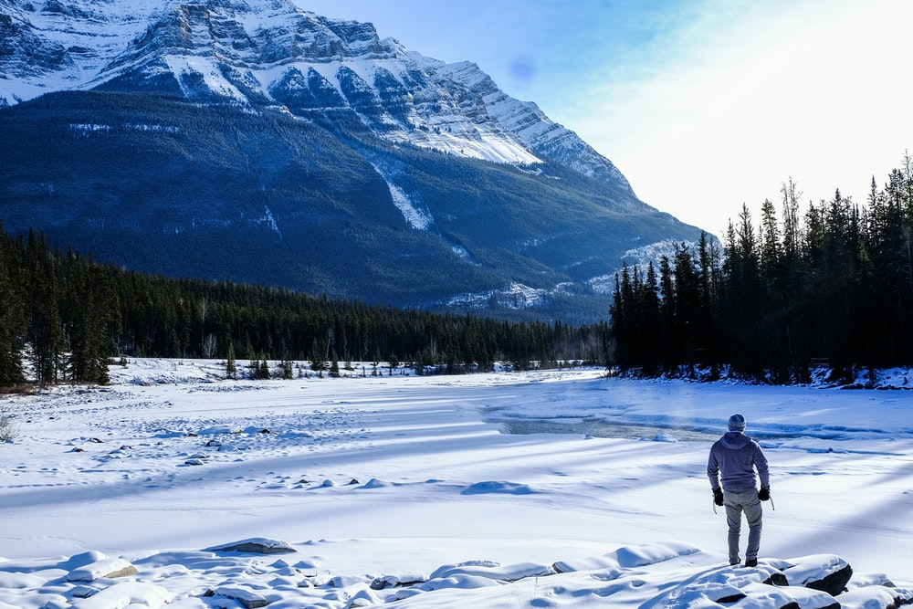 person standing on snow near mountain during daytime