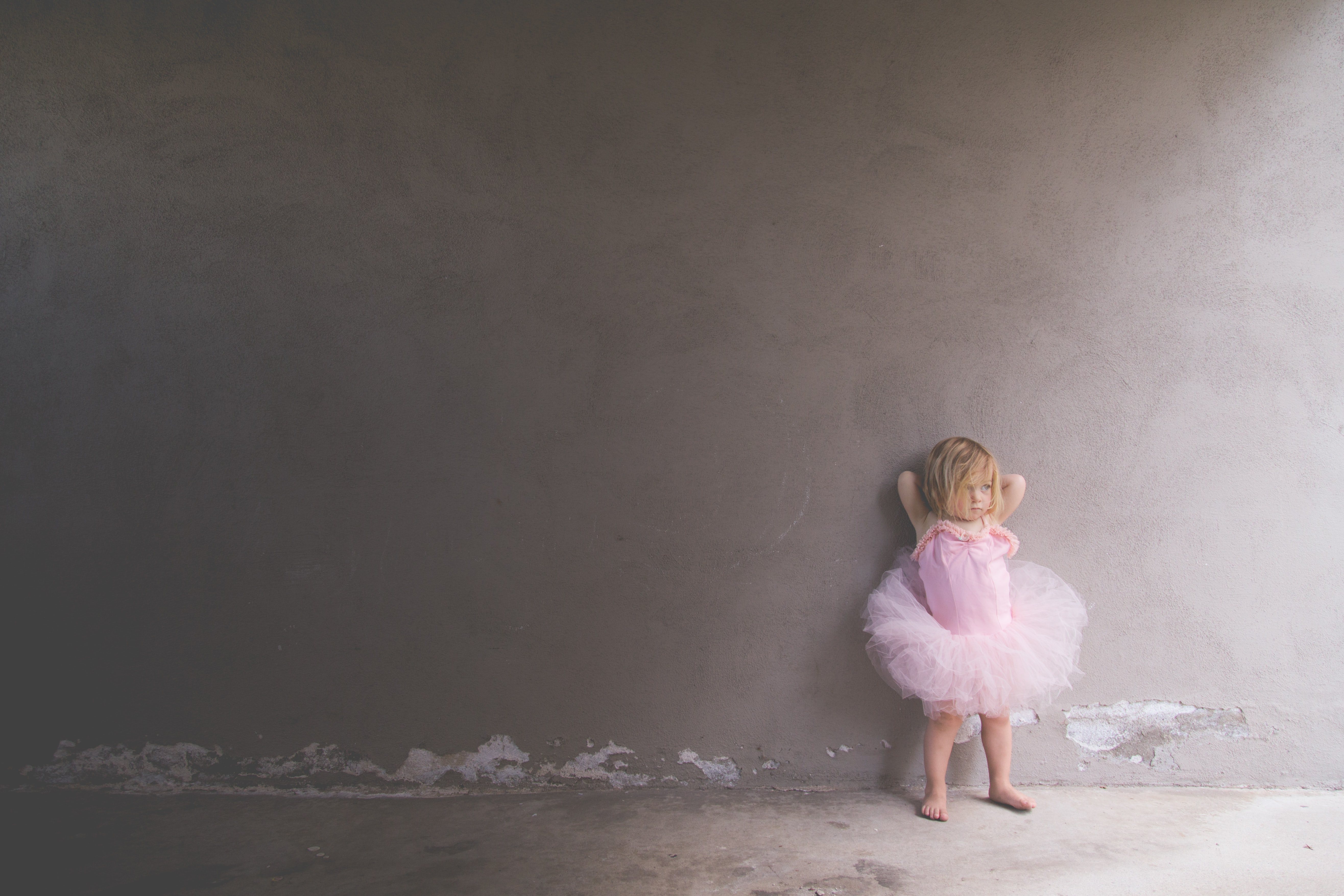 A shadow falls on a child wearing a pink leotard and tutu, leaning against a wall