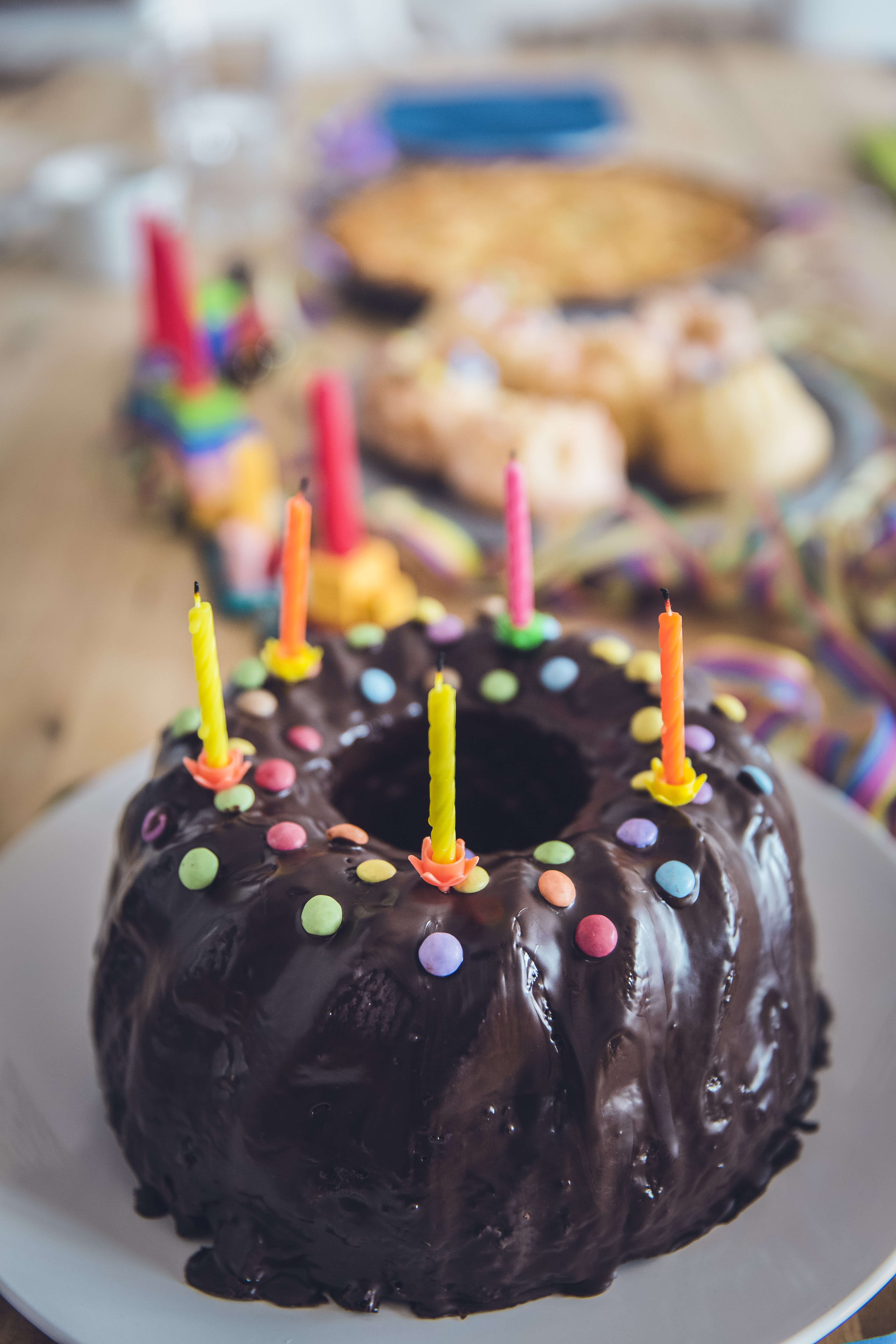A chocolate covered bundt birthday cake with coloured candy and candles on top