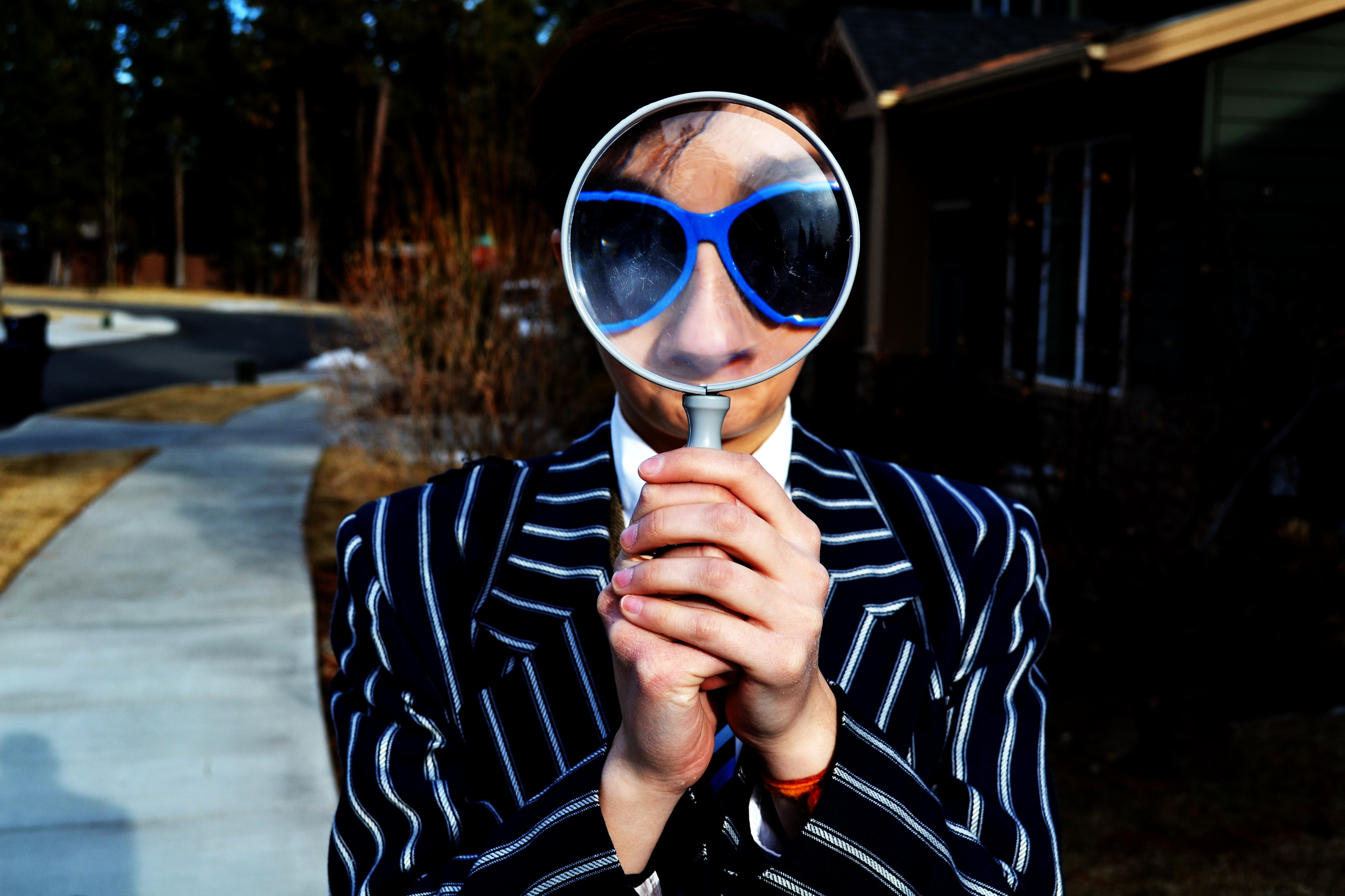 A person holding a magnifying glass, wearing a striped suit and blue sunglasses in Bend