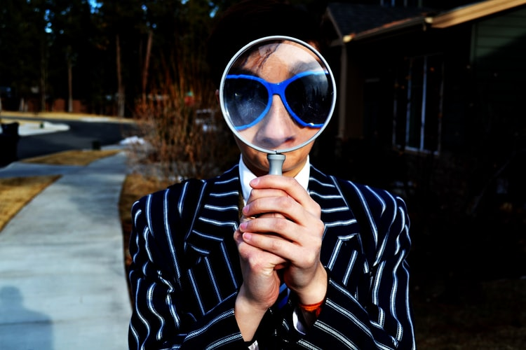 A photo of a woman holding a magnifying glass in front of her face, so her eyes and nose are magnified larger than the rest of her. The overall vibe is fun and playful.