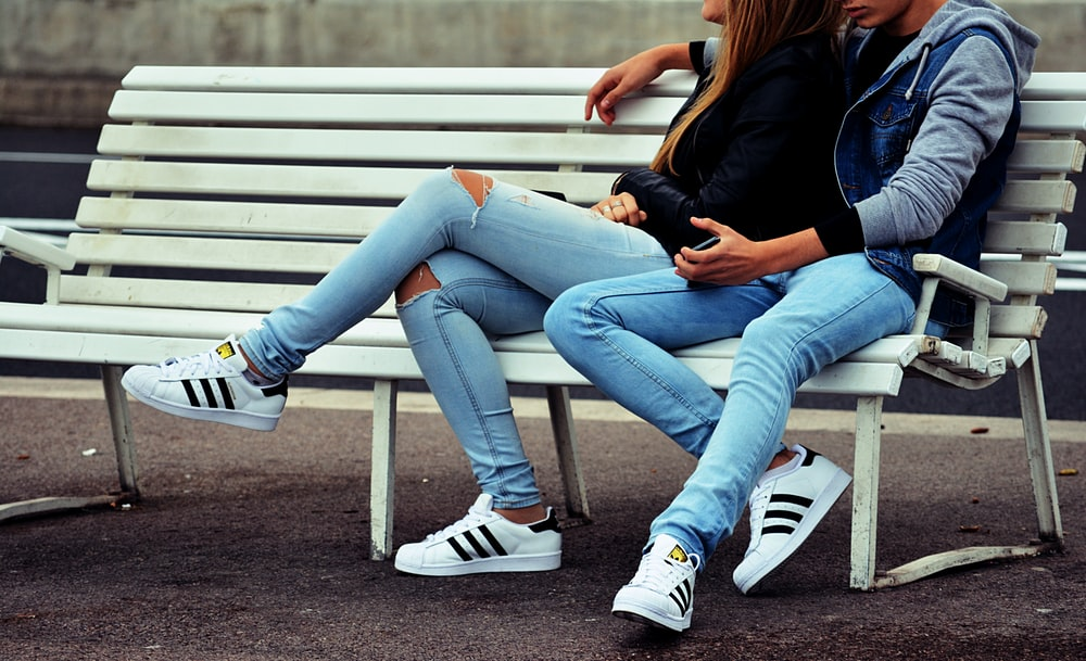 A man puts his hand around a woman in jeans, sitting on a white bench outdoors