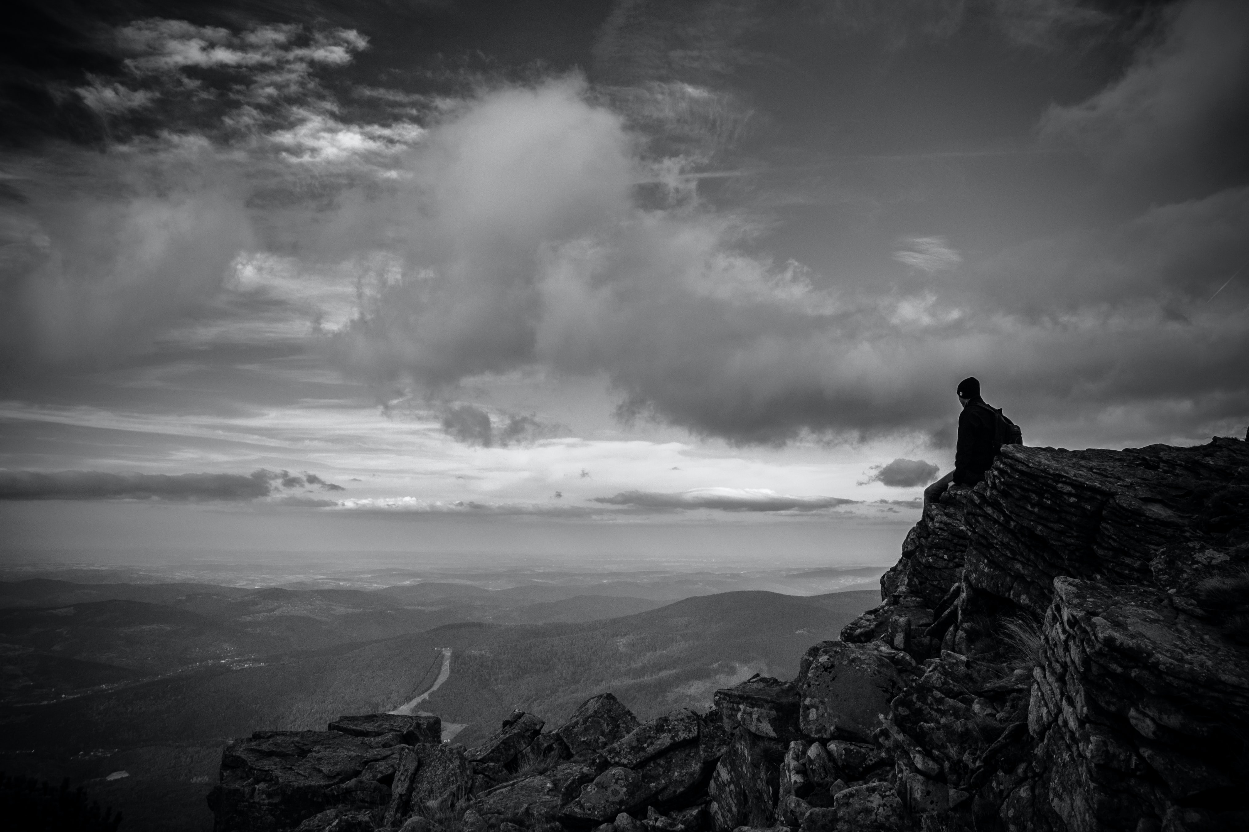 grayscale photography of man sitting on mountain peak under cumulus clouds