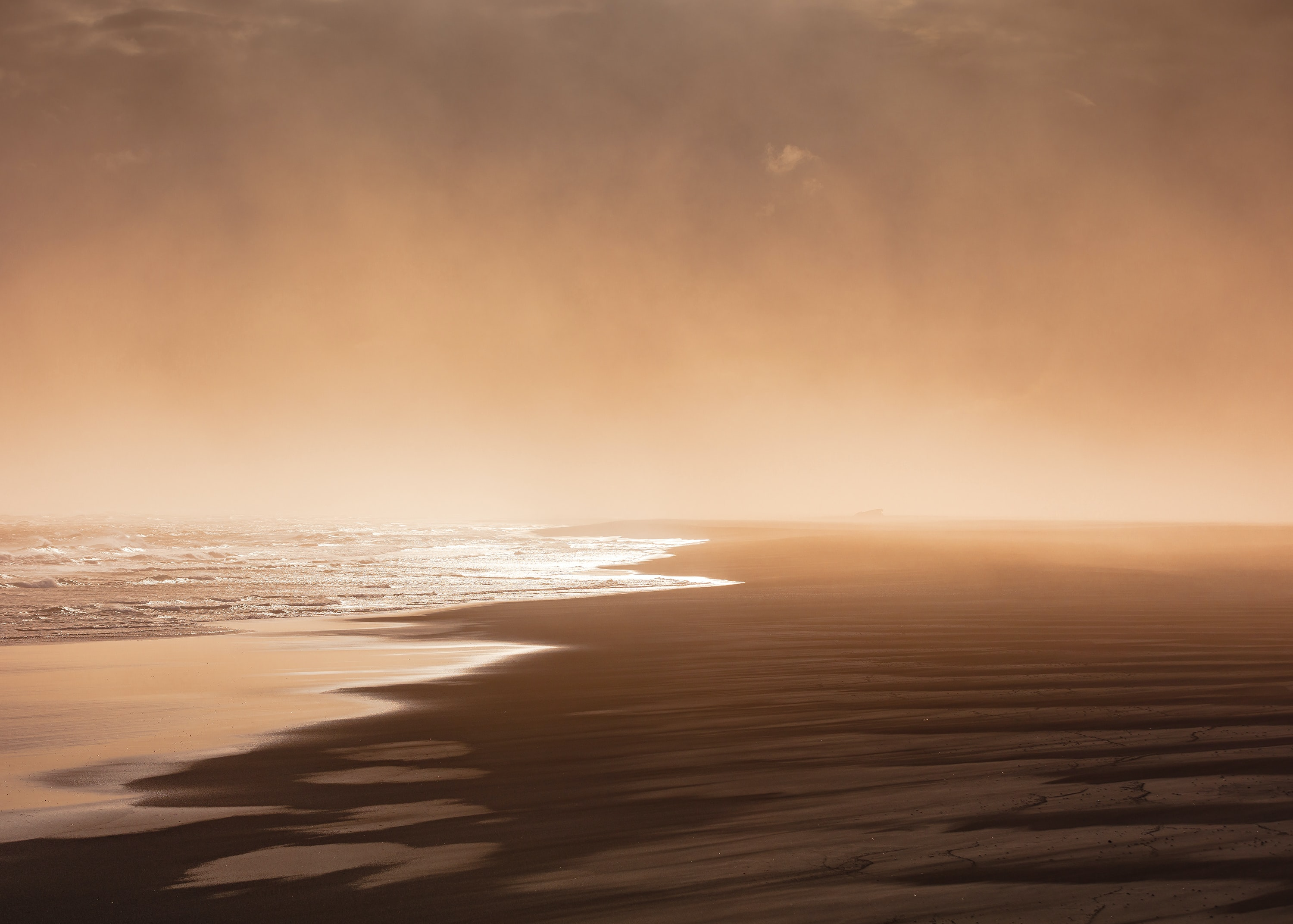 Sunrise through fog from the wet sand beach in Landeyjahöfn