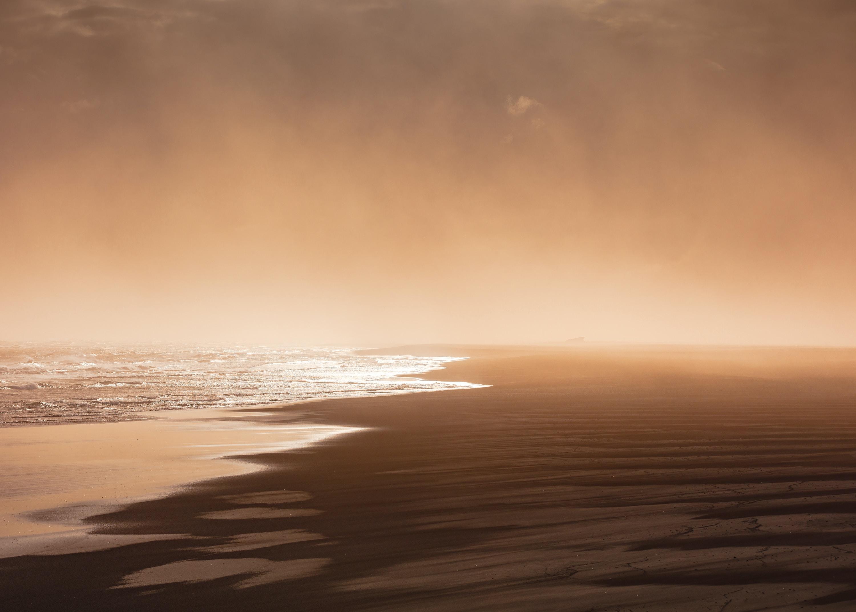 Sunrise through fog from the wet sand beach in Landeyjahöfn
