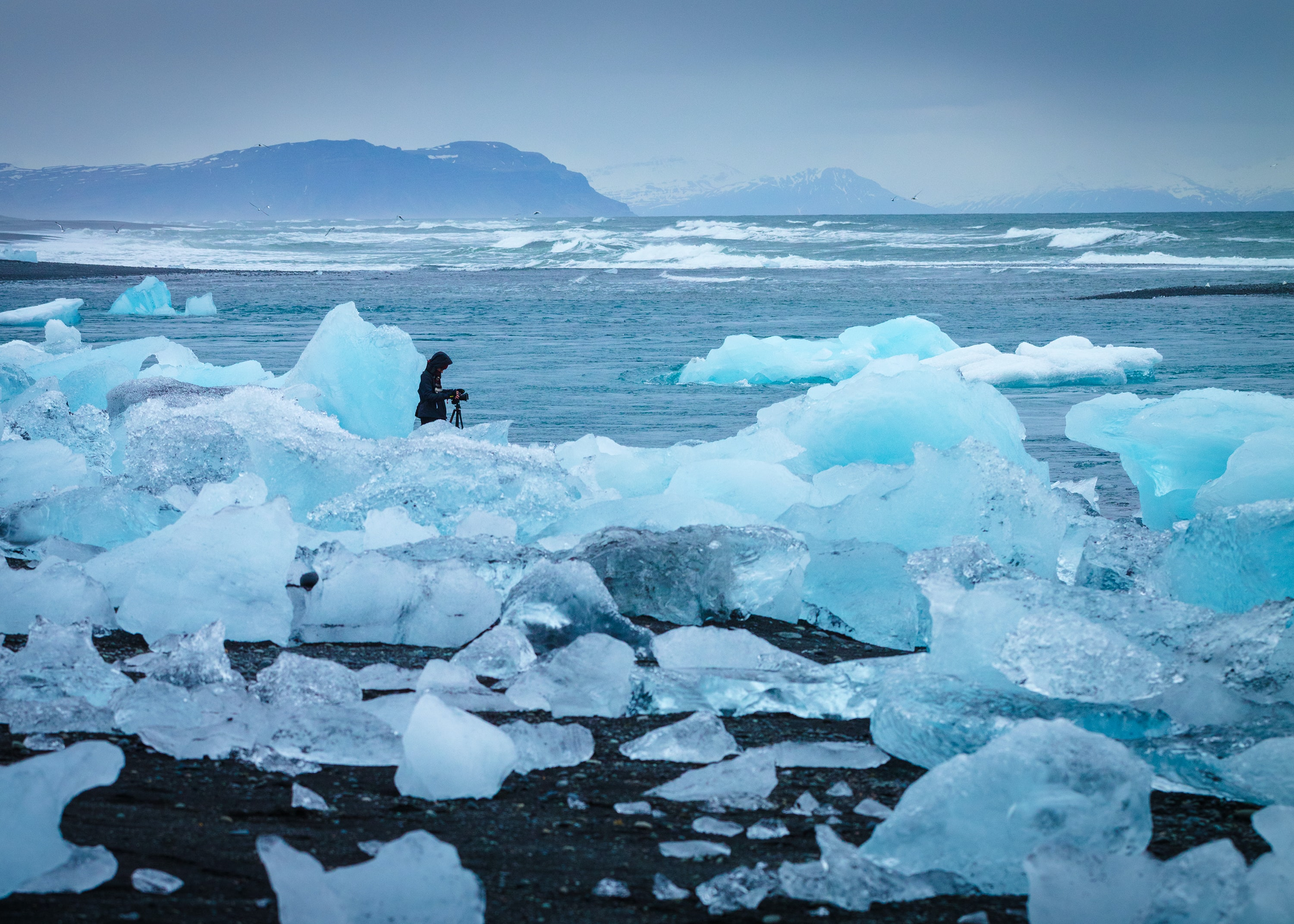 A photographer setting up a camera on a tripod on melting blue glaciers in the ocean
