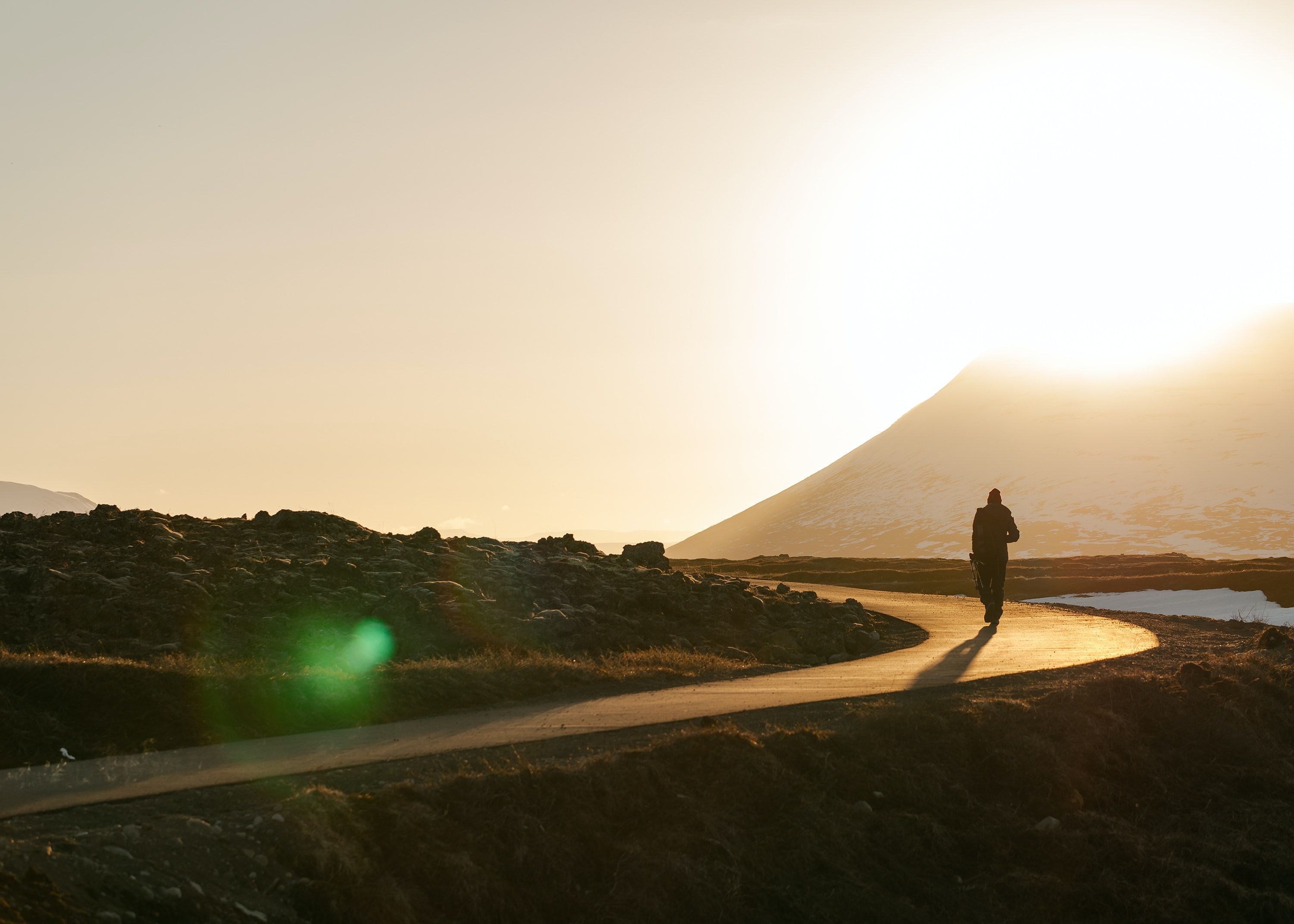 A silhouette of a person walking on a pathway during a sunset in Góðafoss