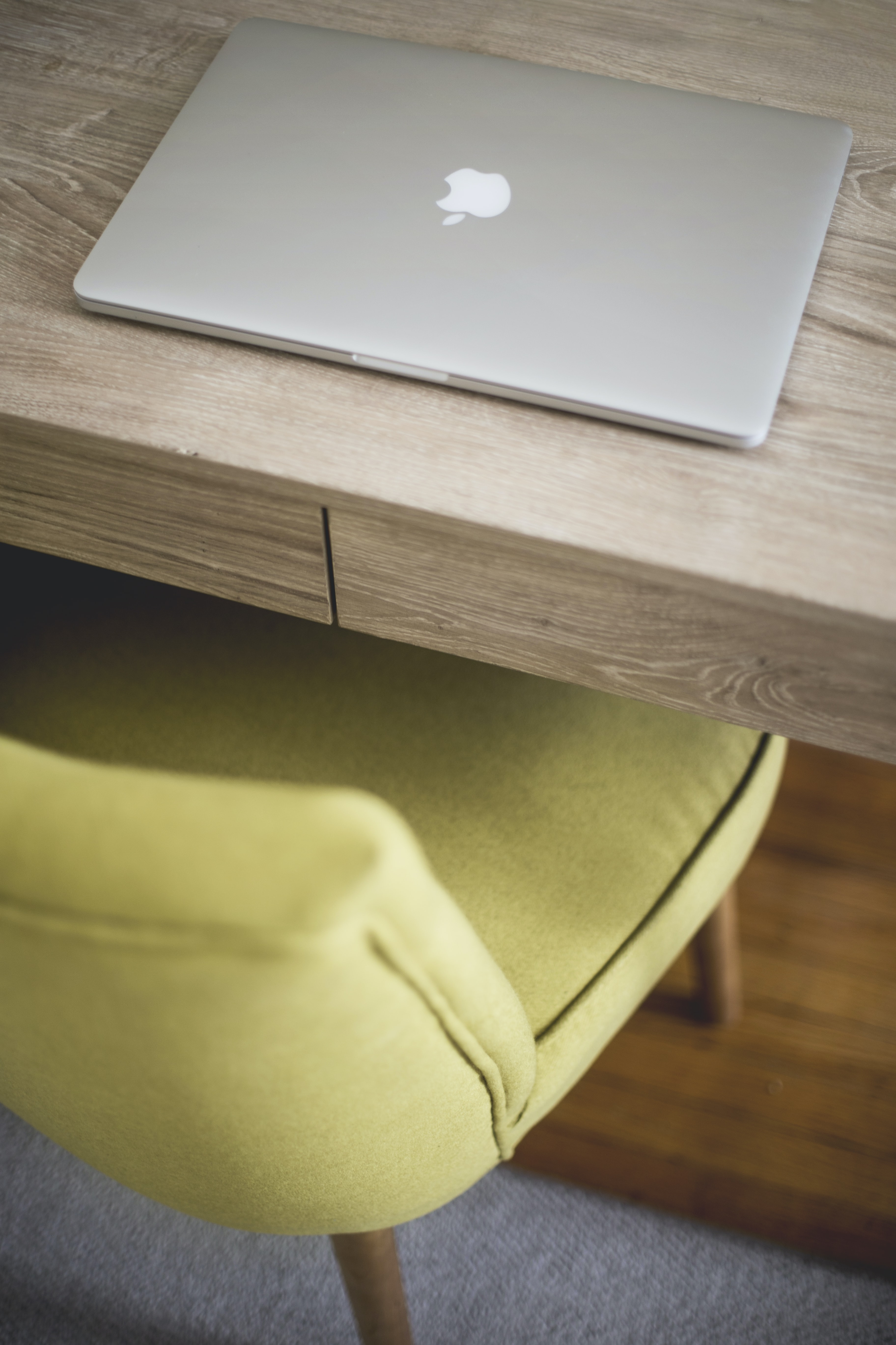 A MacBook on a wooden desk with a green chair