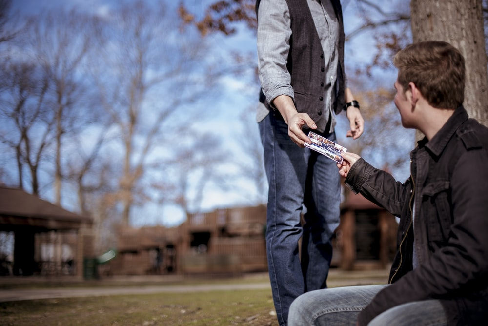 person giving something to man