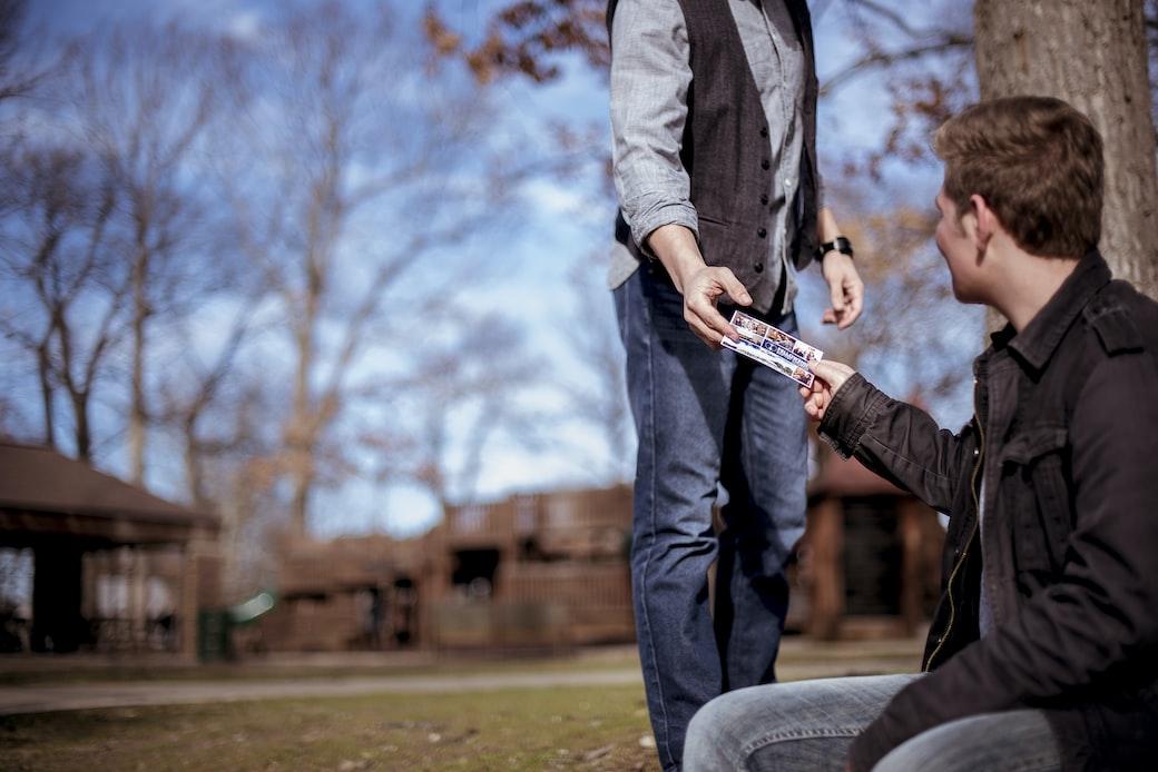 Standing Man Passing Paper to Sitting Man