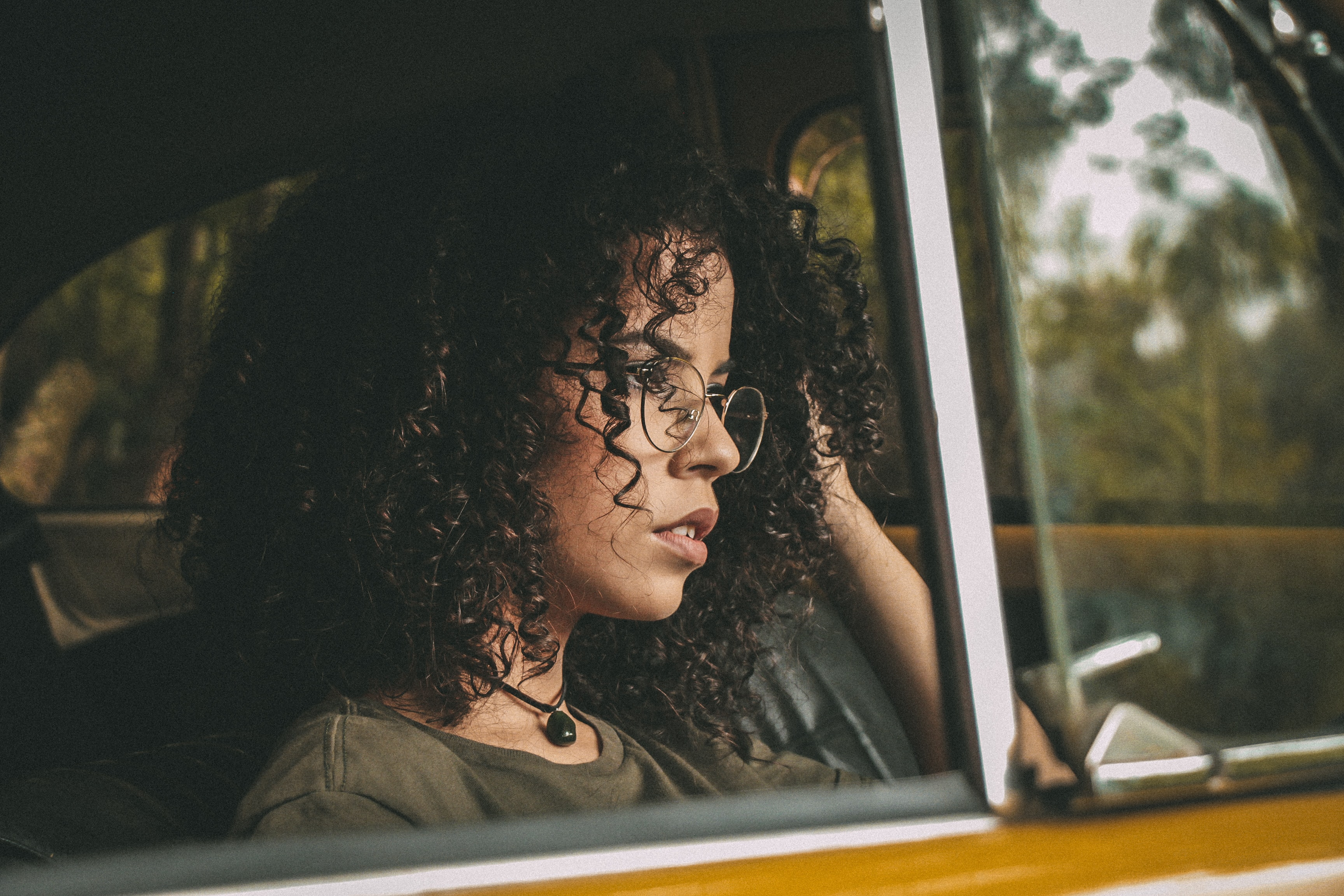 Woman with curly hair and vintage glasses staring out a car window
