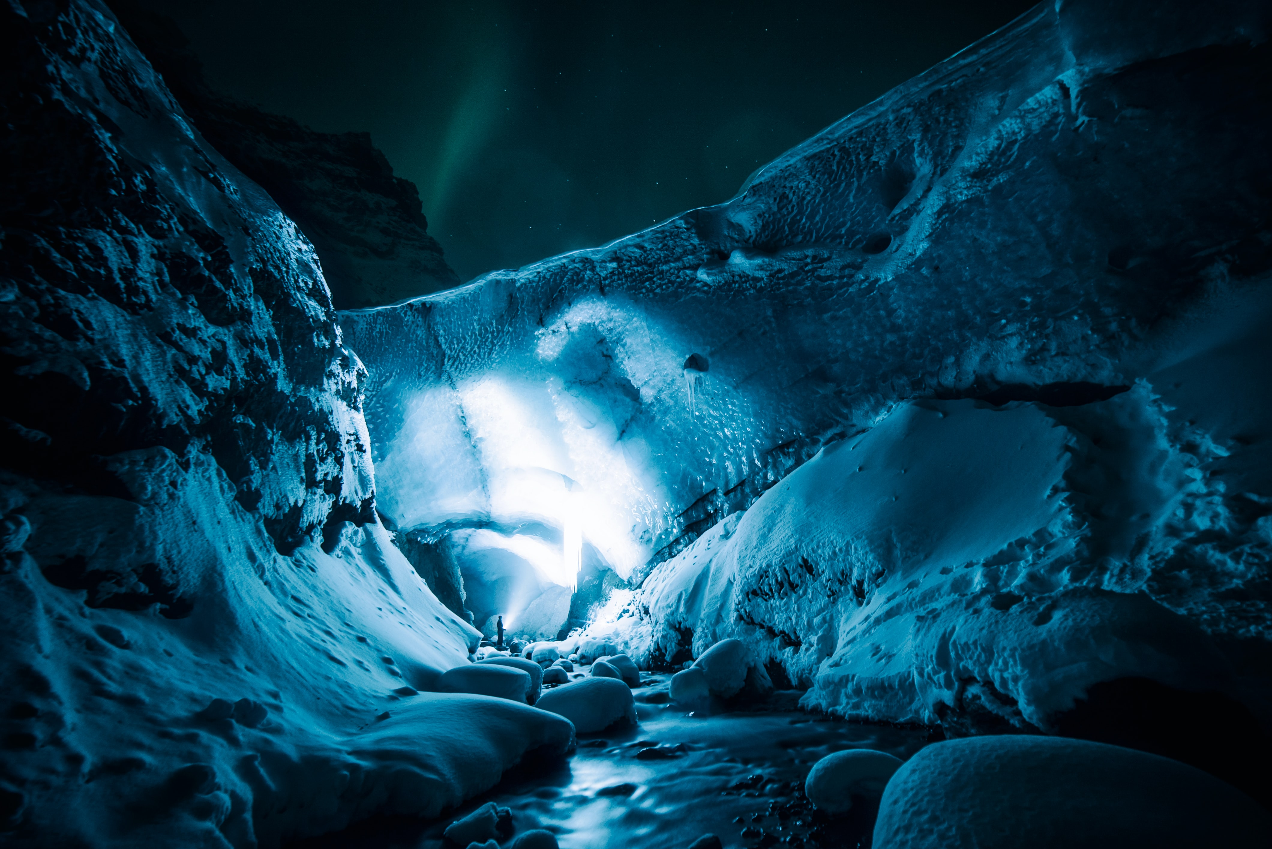 A view inside the Gigjökull Ice Cave in Iceland, highlighted with a blue light