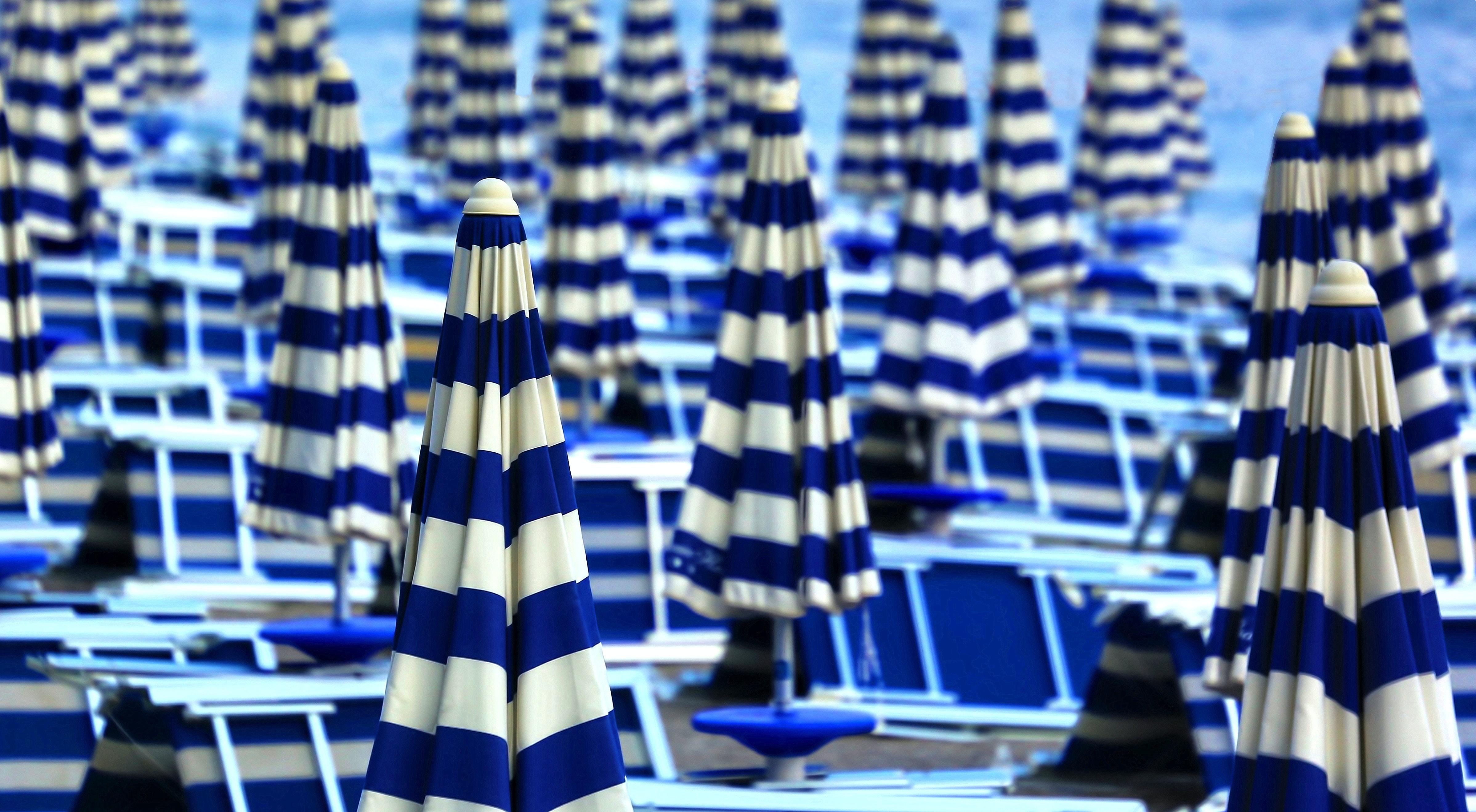 A beach with blue and white picnic tables and umbrellas in Sapore di' Mare
