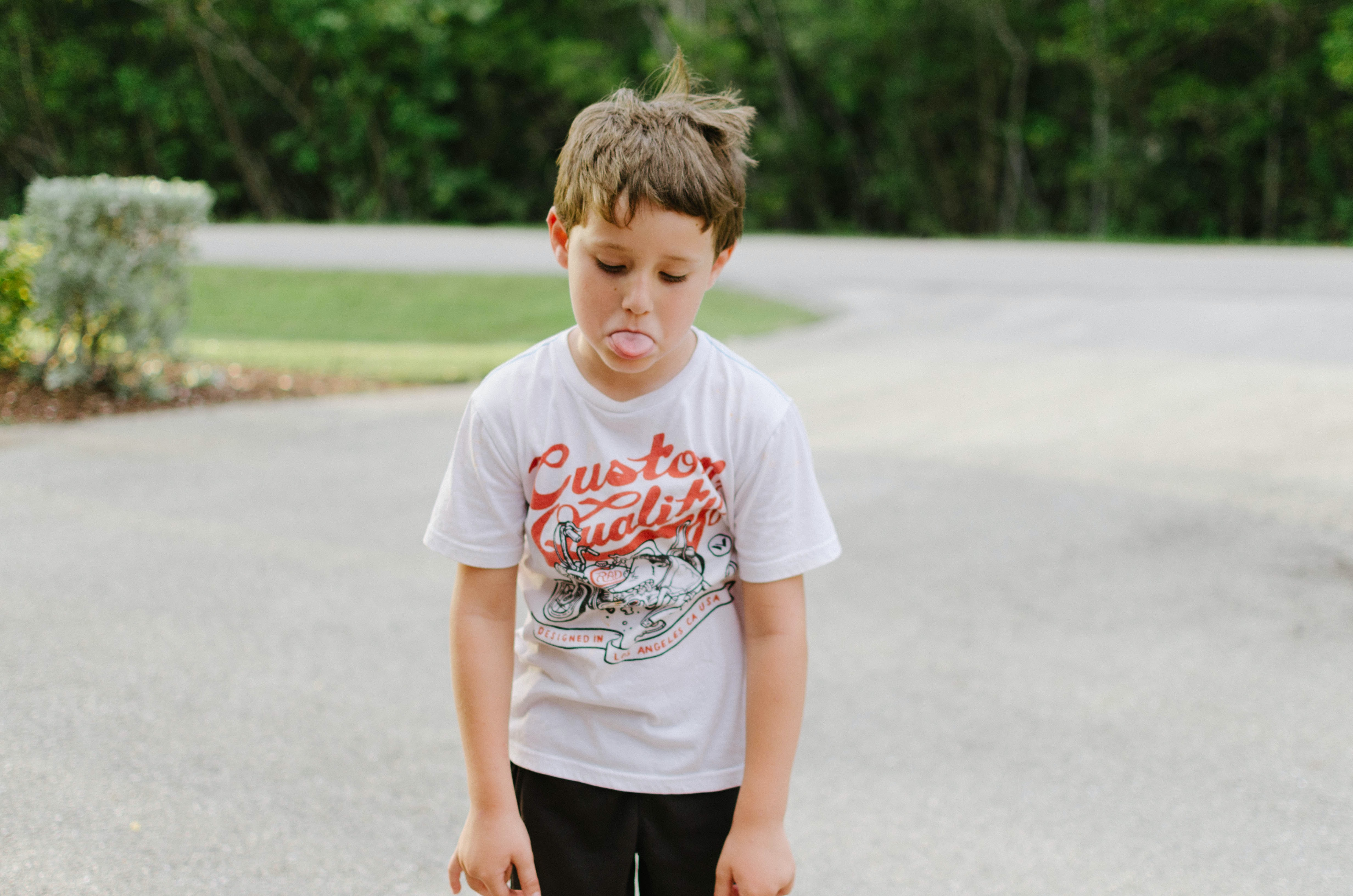 boy standing on gray concrete road while tongue out