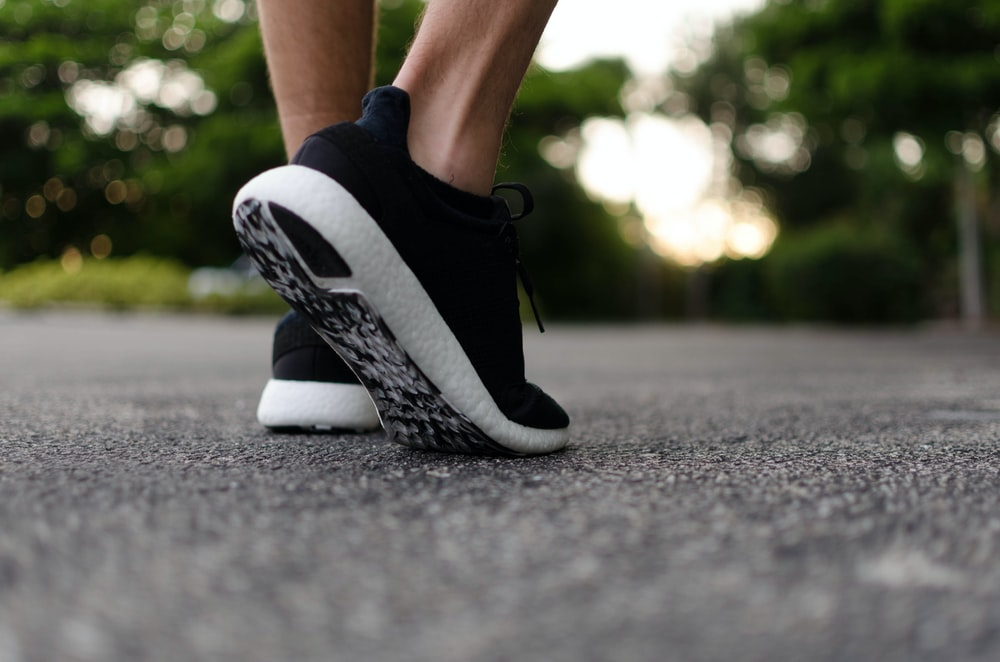The sole of a pair of black and white shoes, taken from close up as someone lifts their foot to walk.