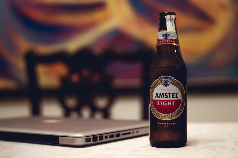 Amstel Light beer bottle near laptop computer