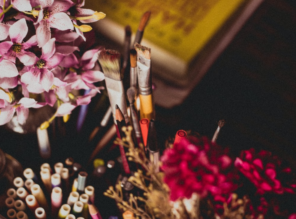 selective focus photography of makeup brush and pencil and pens beside pink and purple flowers