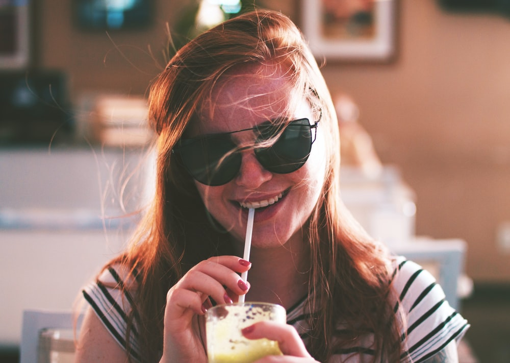 woman sipping drink while smiling