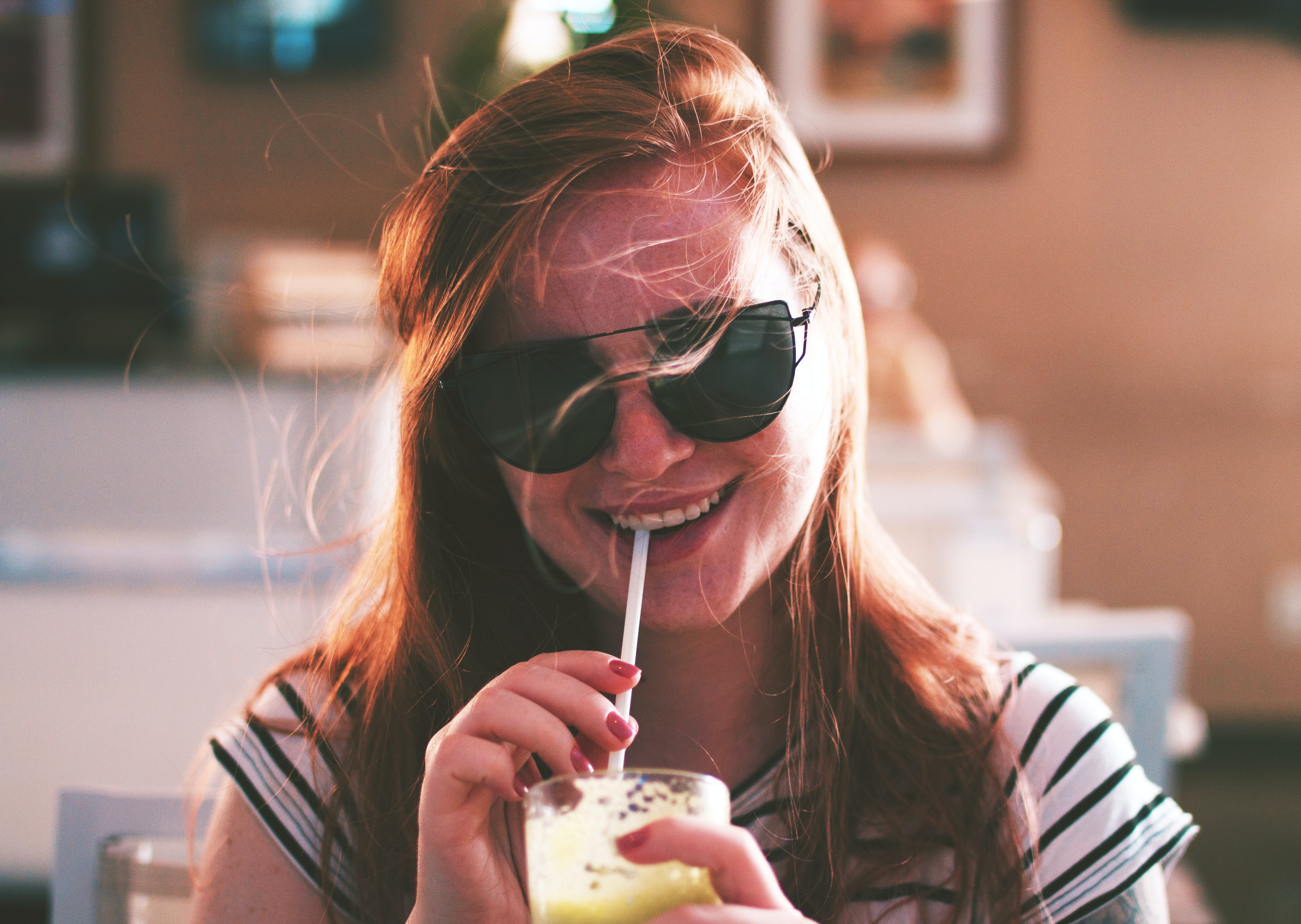 A smiling woman with sunglasses and windswept hair drinks from a straw in a Natal cafe